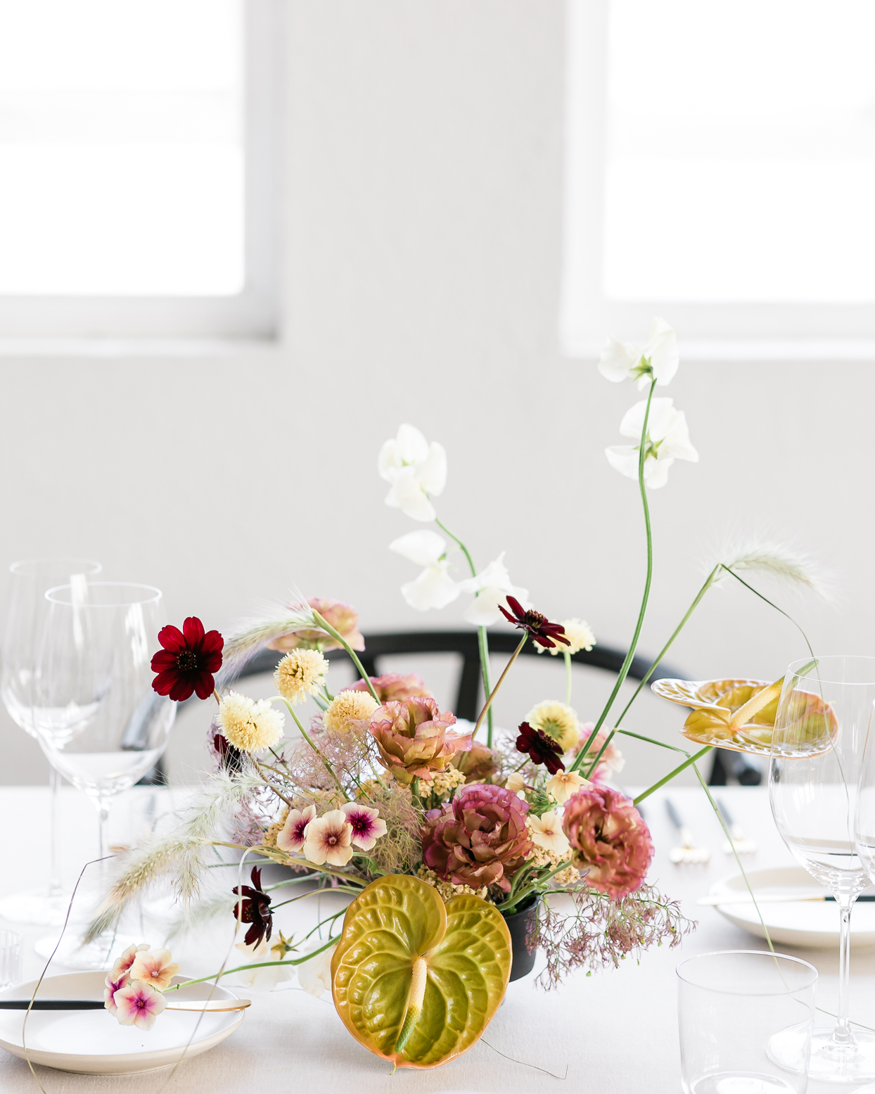 wedding reception centerpiece of greenish-gold anthurium lilies and delicate rich-toned wildflowers