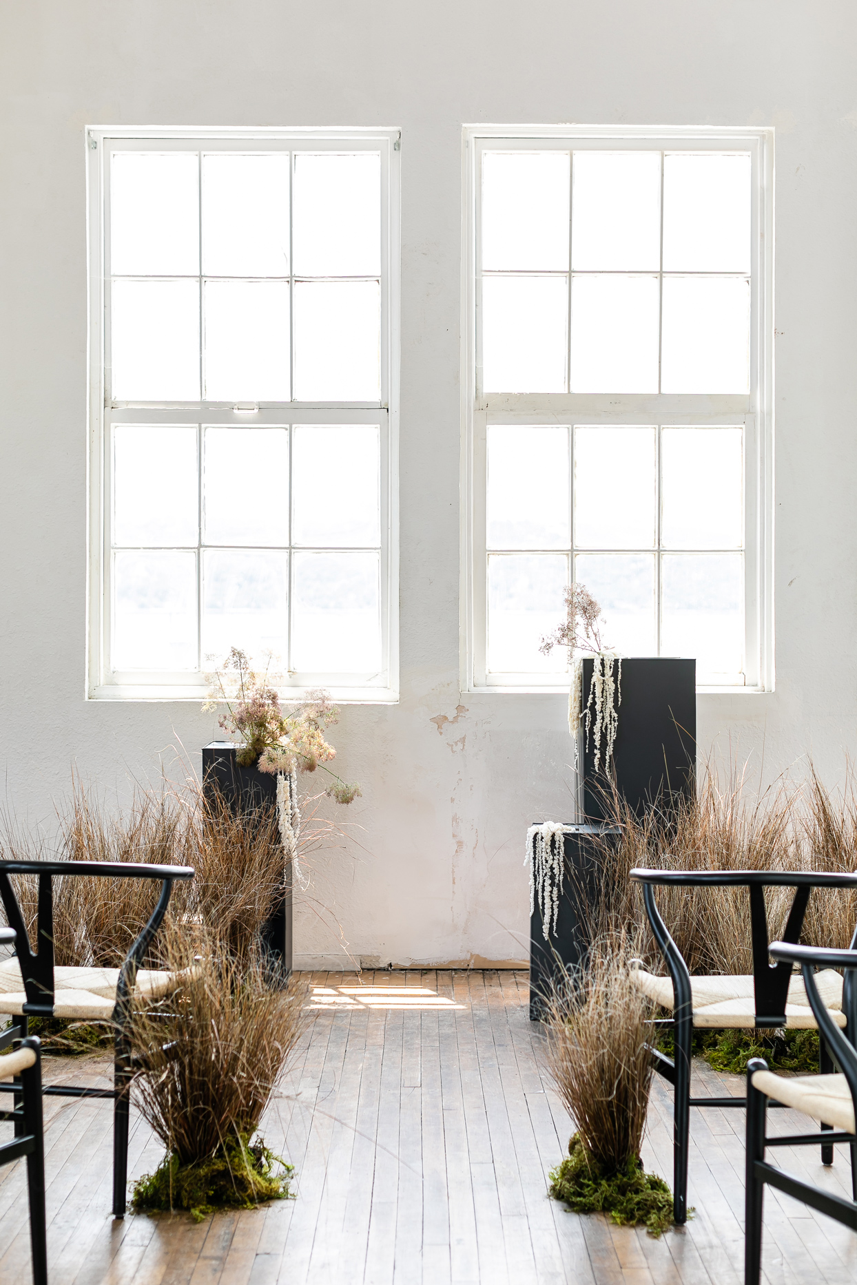 neutral industrial space embellished with dried grasses and draped florals