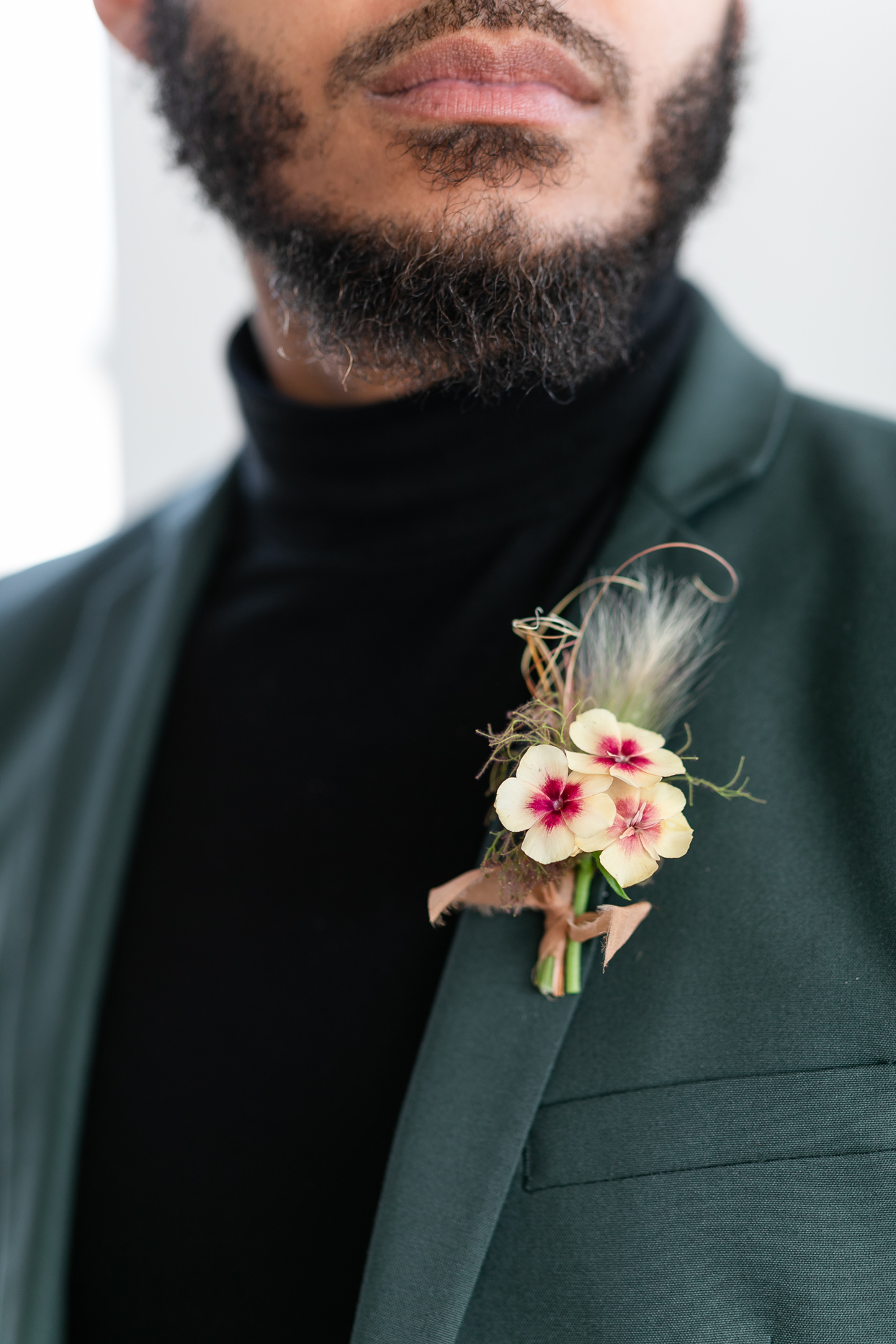 groom wearing turtleneck and delicate ivory flower boutonniere