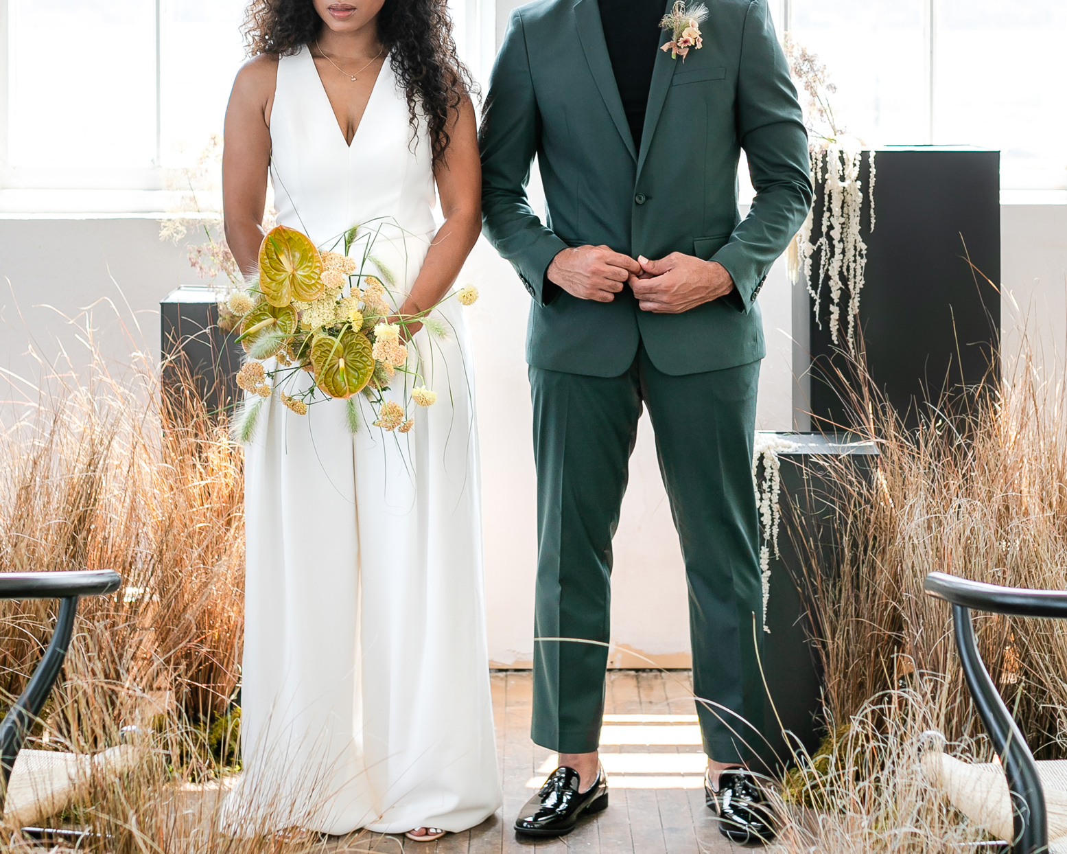 bride wearing jumpsuit and groom wearing green tux