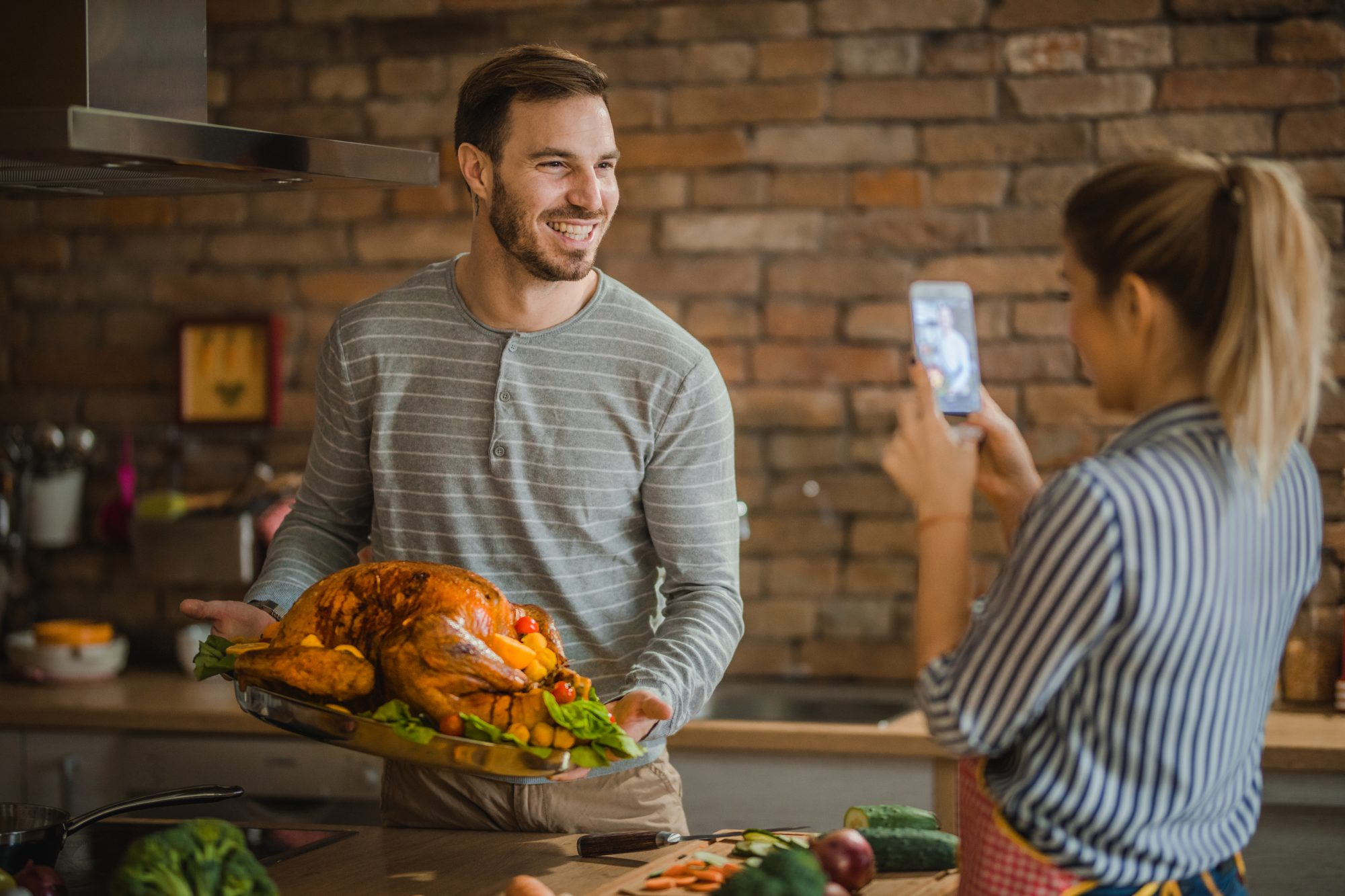 Happy man being photographed with Thanksgiving turkey by his girlfriend in the kitchen