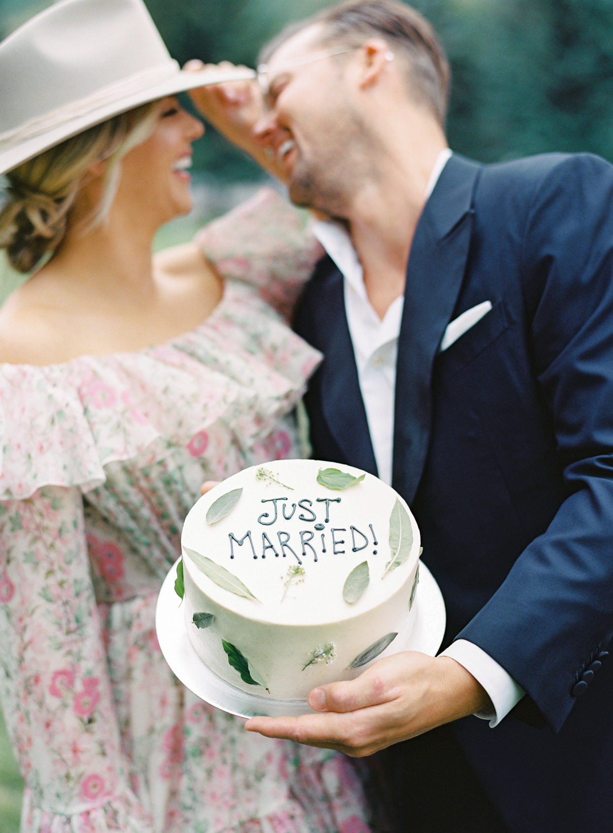 """bride and groom holding """"just married"""" wedding cake"""
