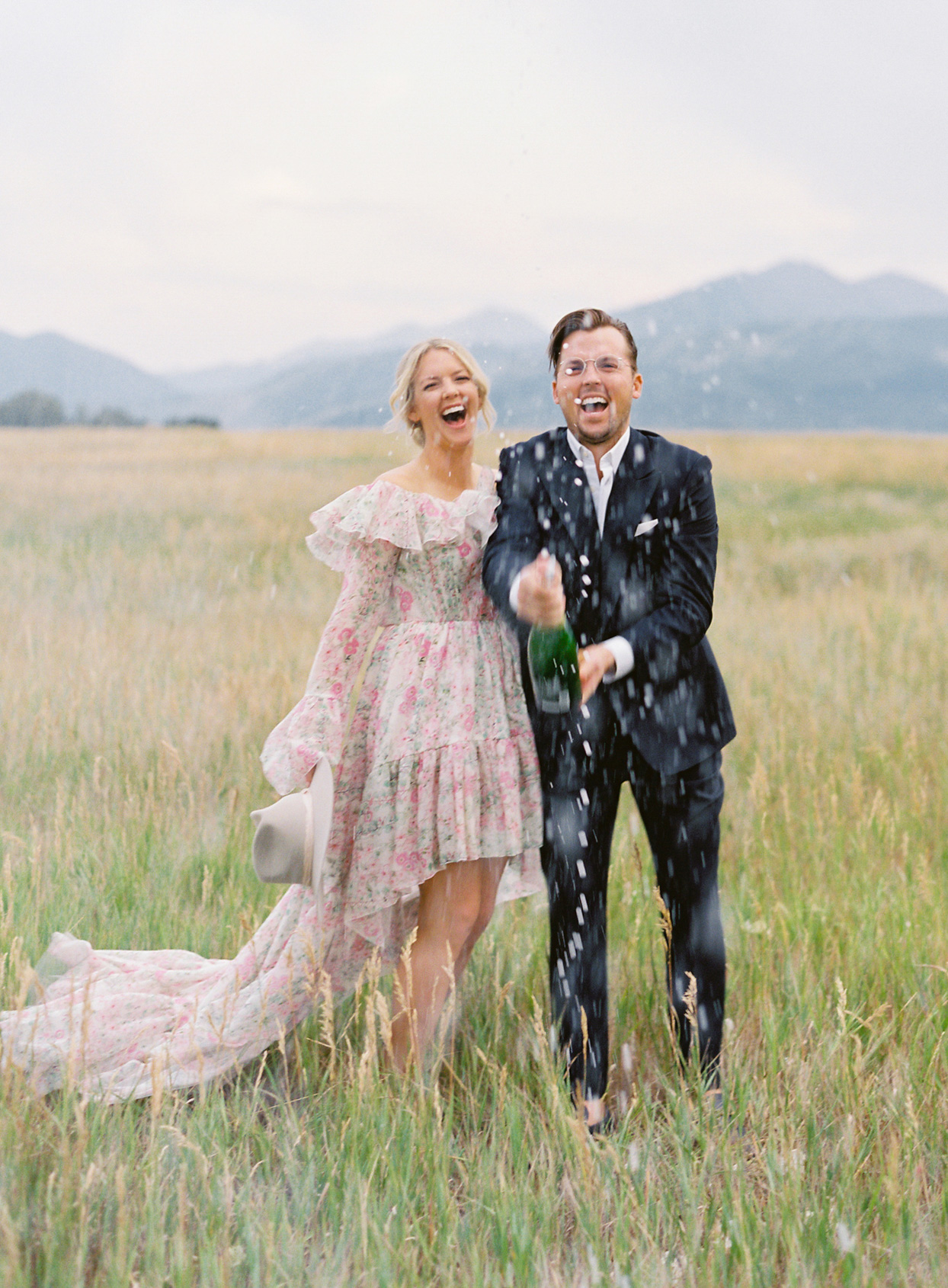 bride and groom popping champagne in a field
