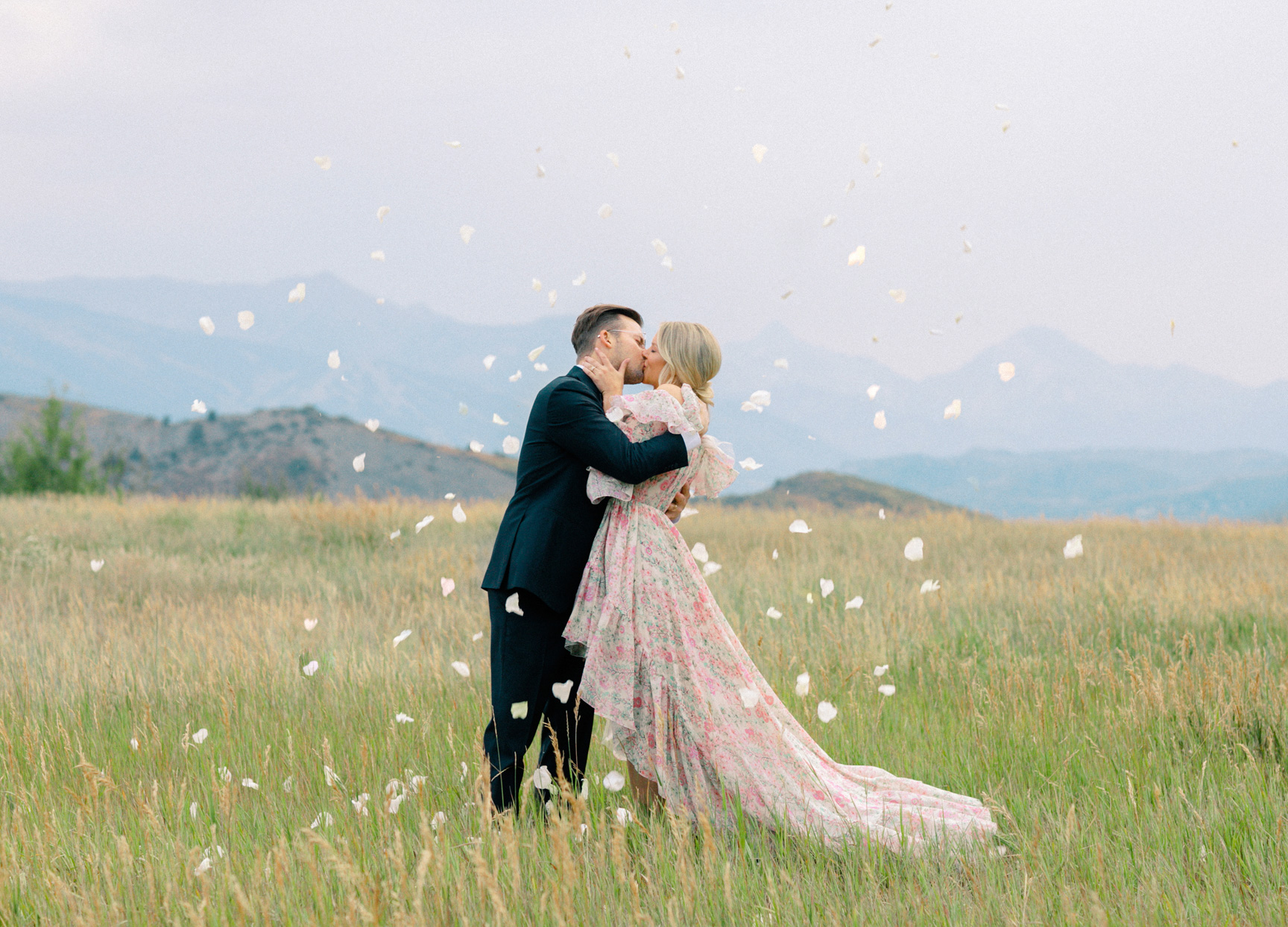 bride and groom kissing in field with flower petals
