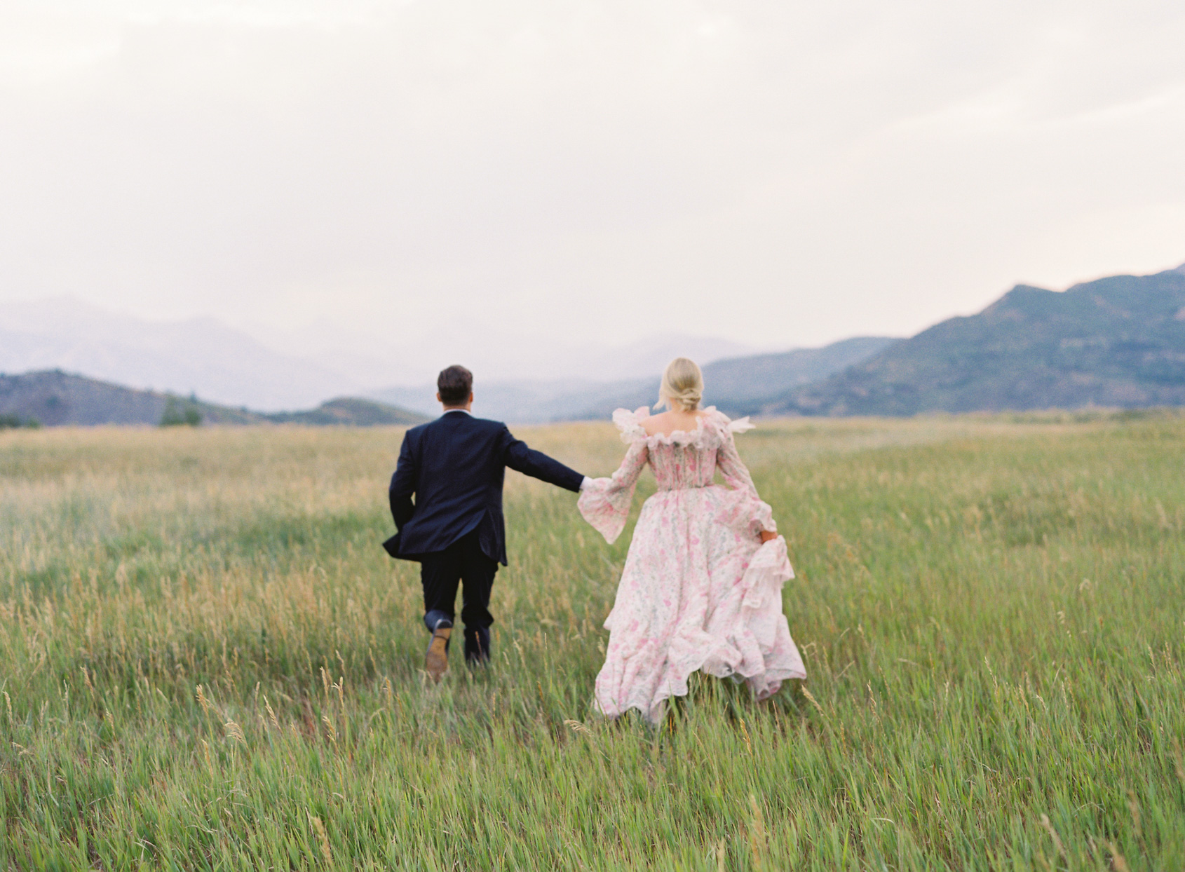 bride and groom holding hands and running through field