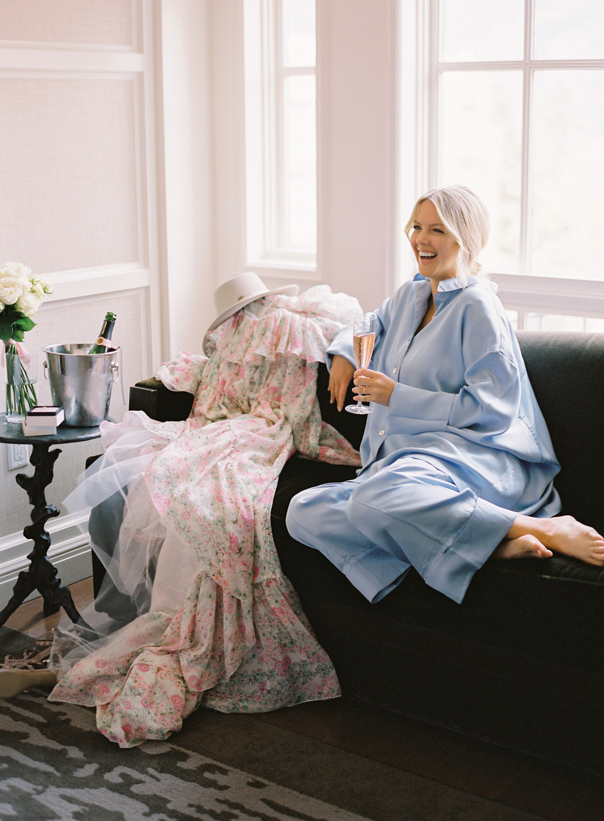 bride in blue silk pajamas sitting on couch drinking champagne