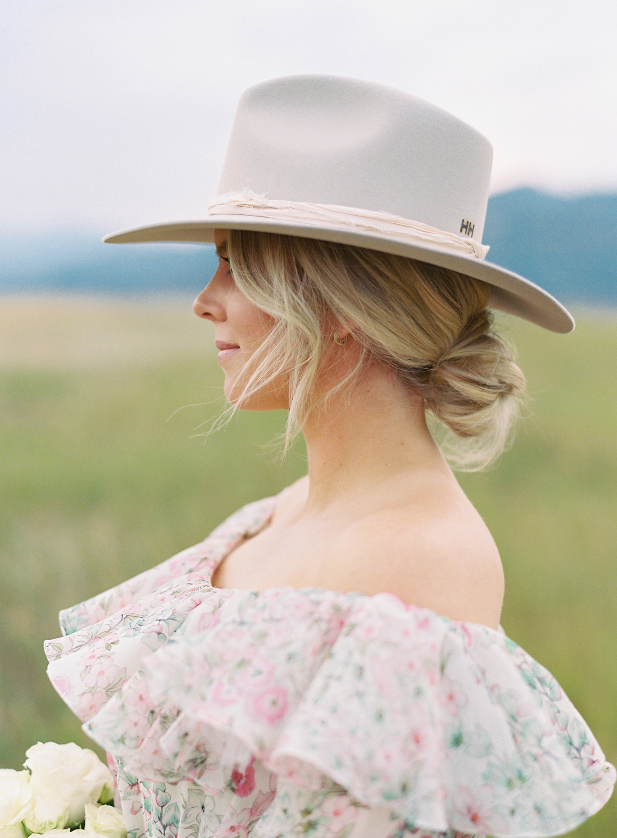 bride in floral pink dress and cream colored hat