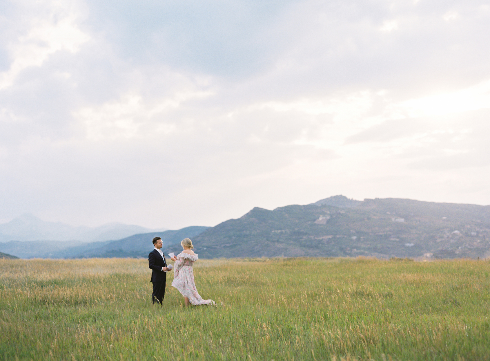 exchanging vows in field with mountain backdrop