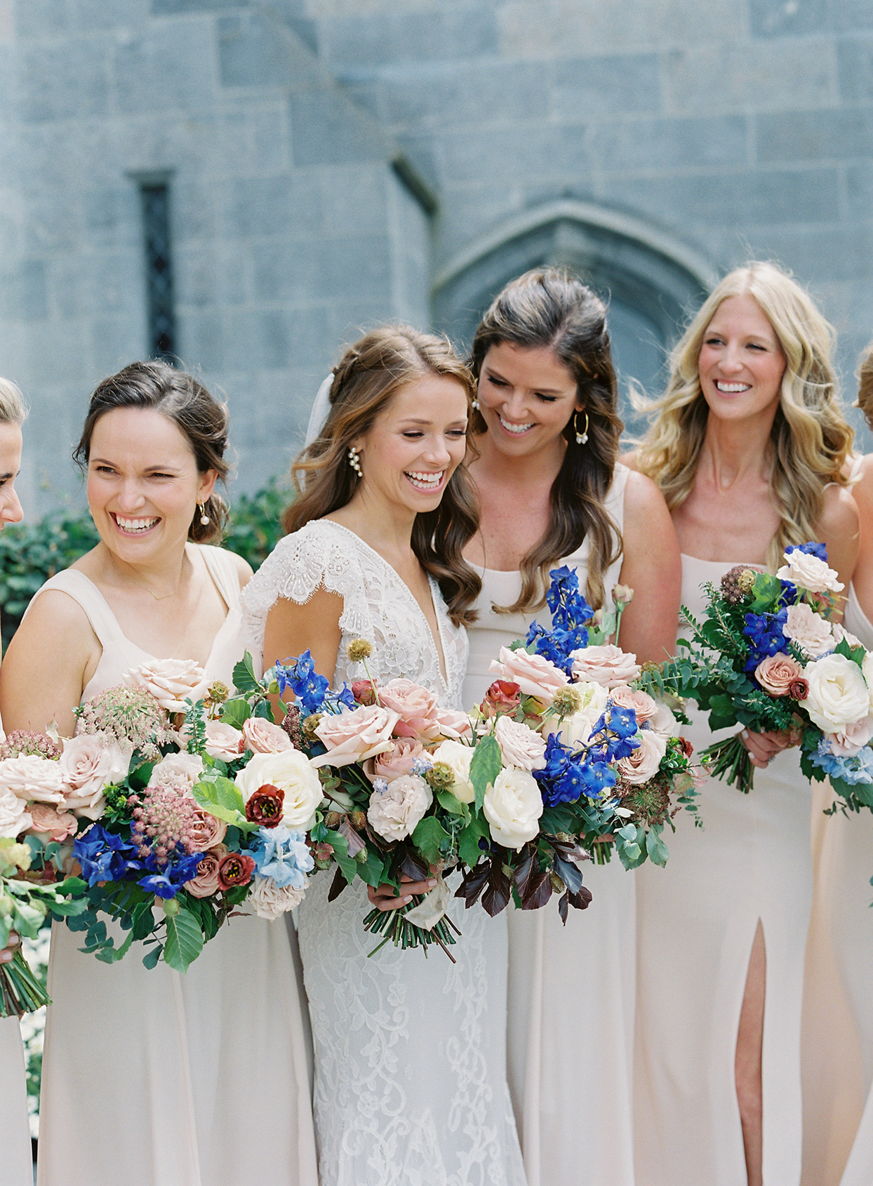 bride smiling with bridesmaids wearing various styled dresses