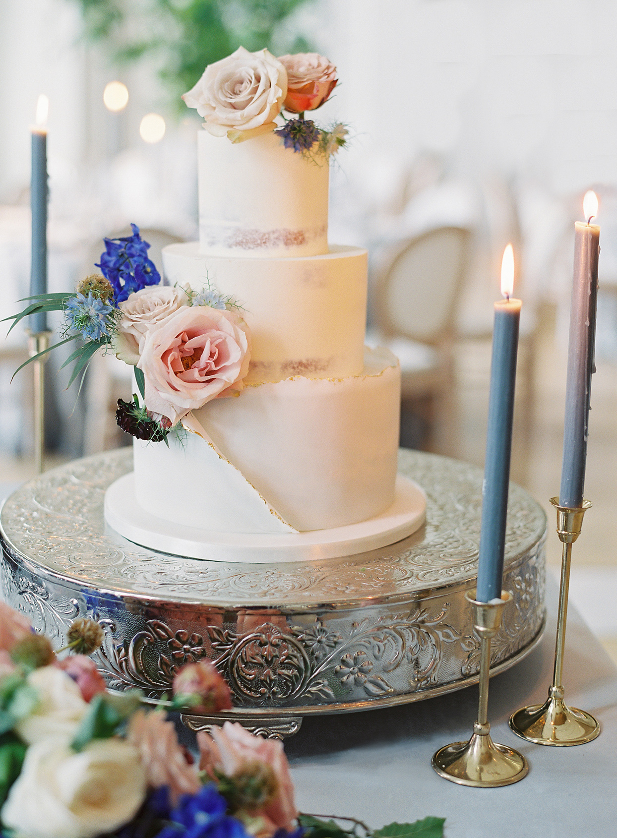 three tiered white frosted wedding cake with floral details