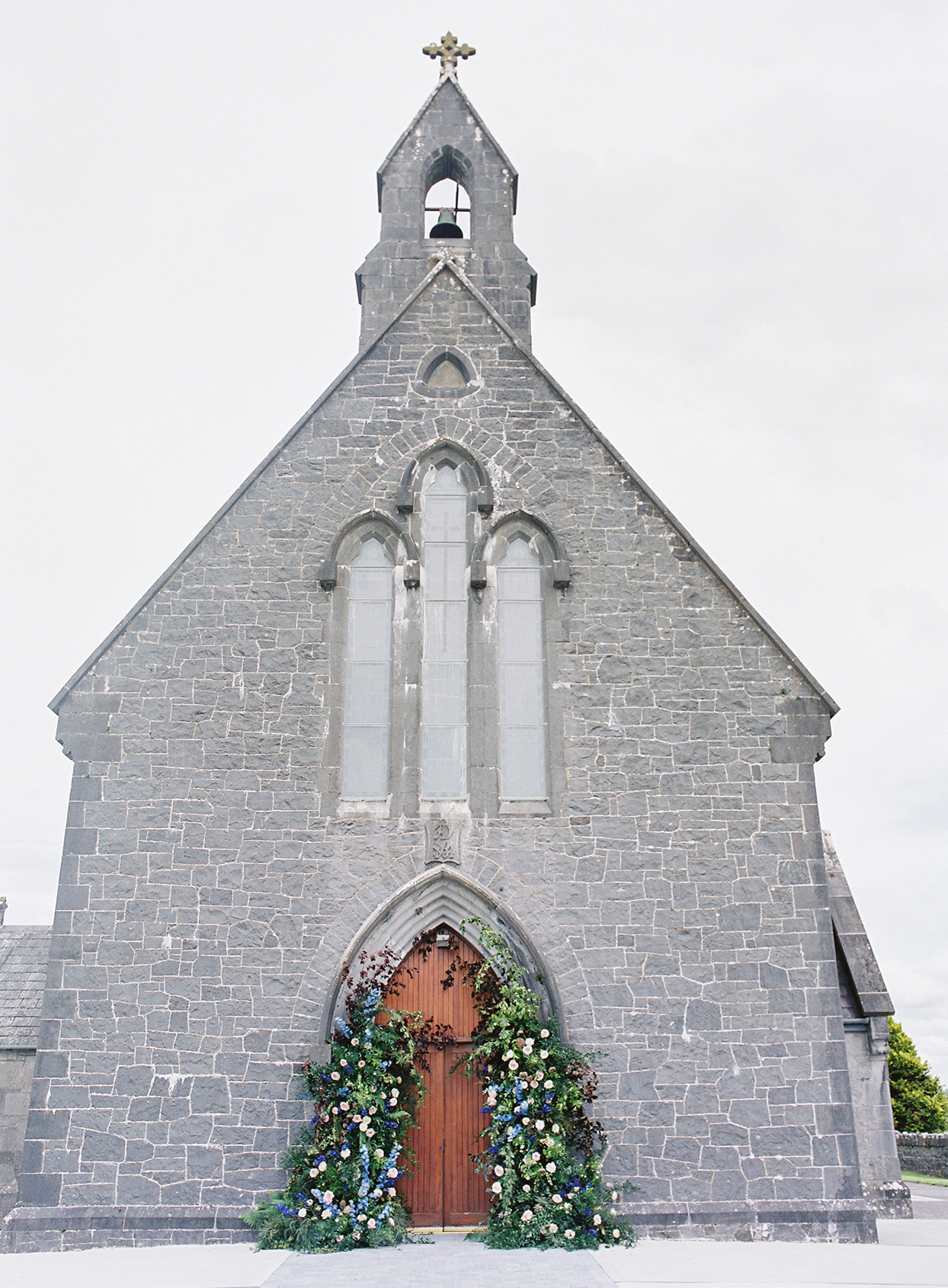 grey stone church building with floral and greenery display on front door