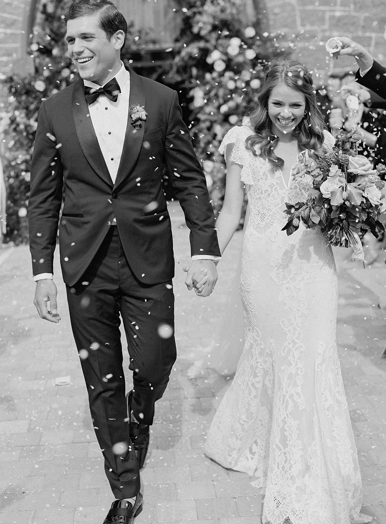 bride and groom smiling holding hands under confetti during church exit