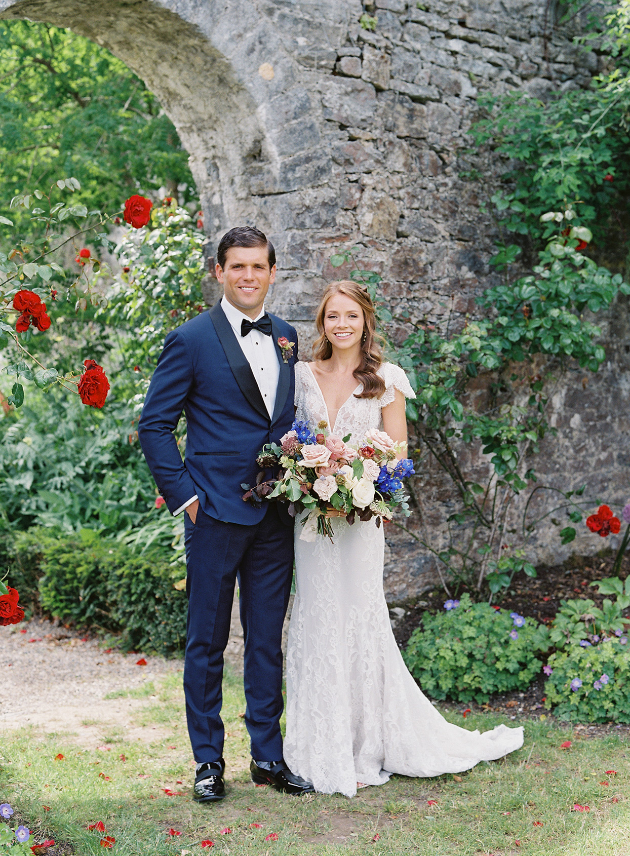 bride and groom next to stone archway outside in garden