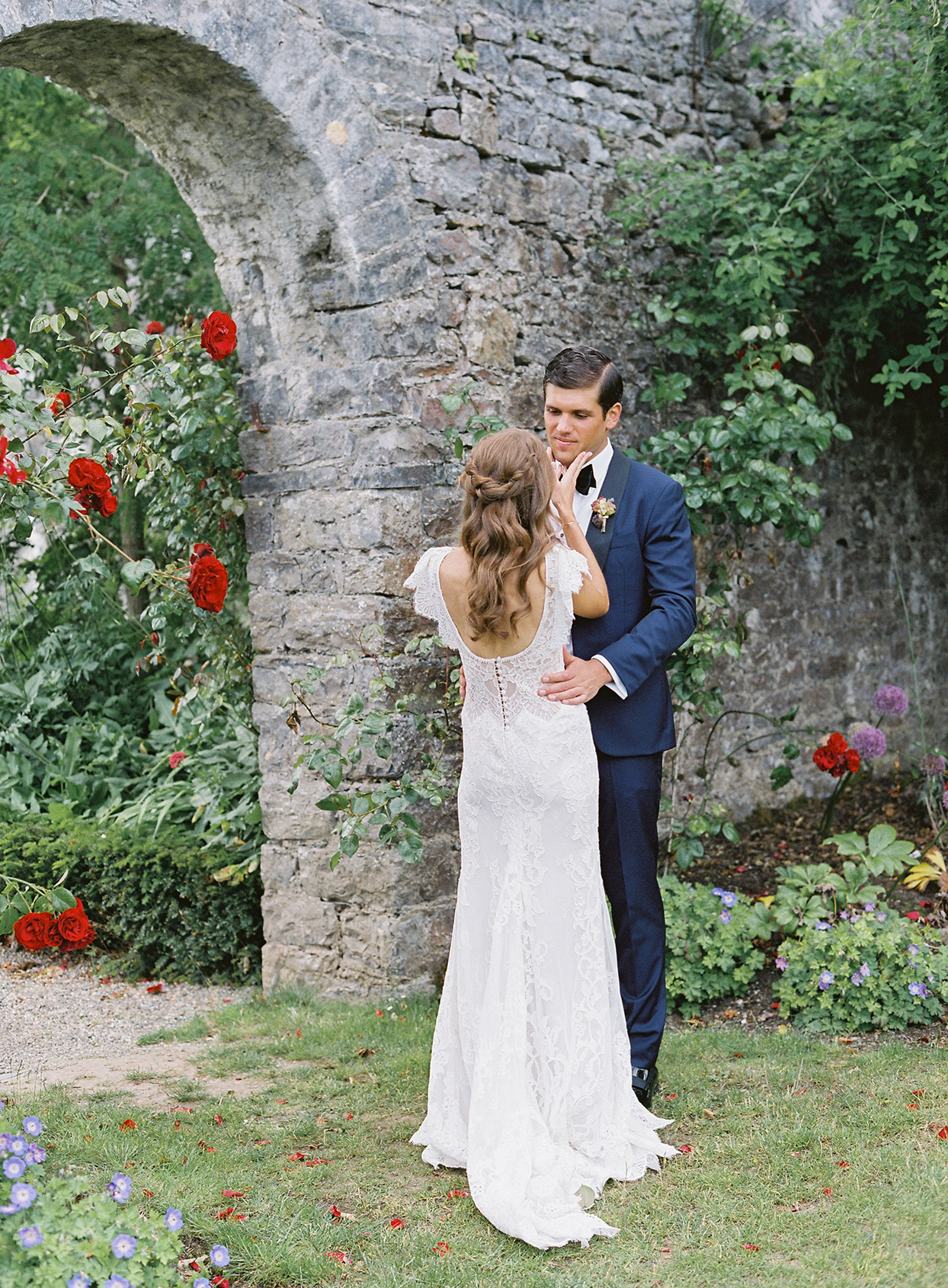 bride holding grooms face during first look in garden area