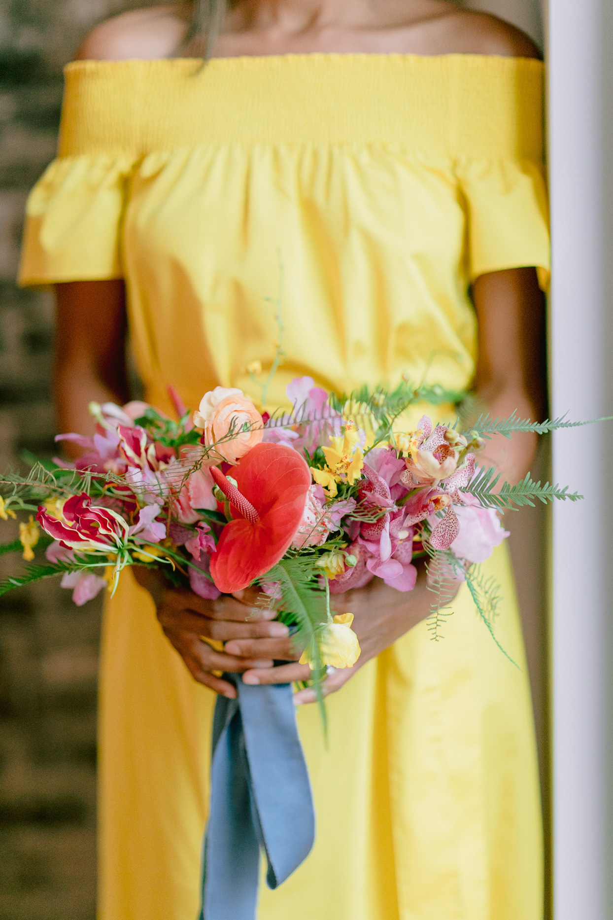 bride in yellow dress holding unique pink and orange floral bouquet