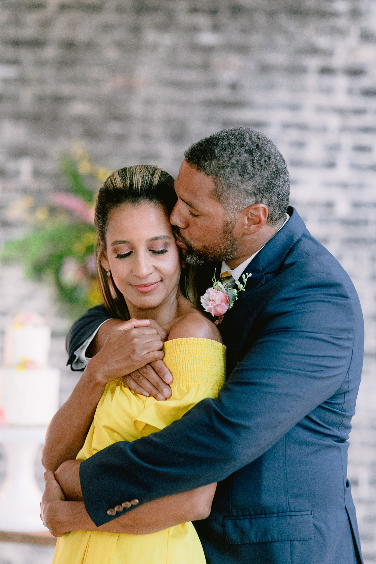 bride in yellow dress and groom embracing for portrait