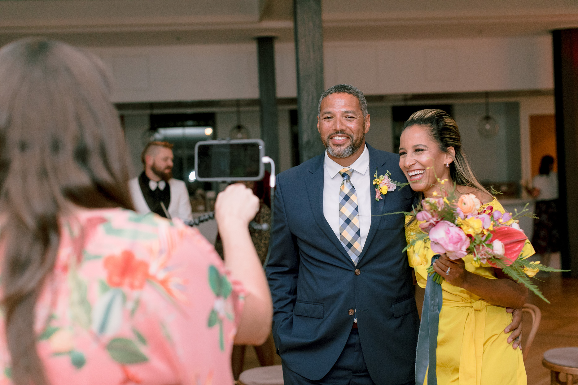 couple smiling for phone virtual wedding ceremony