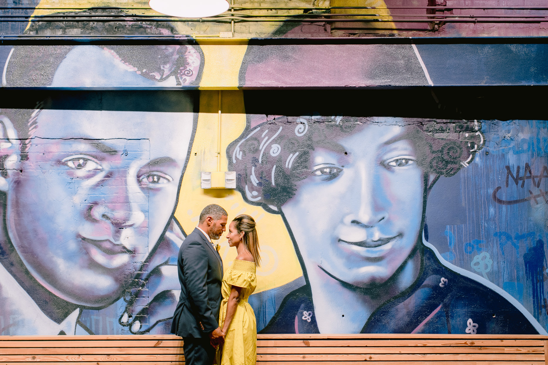 couple portrait in front of mural wall