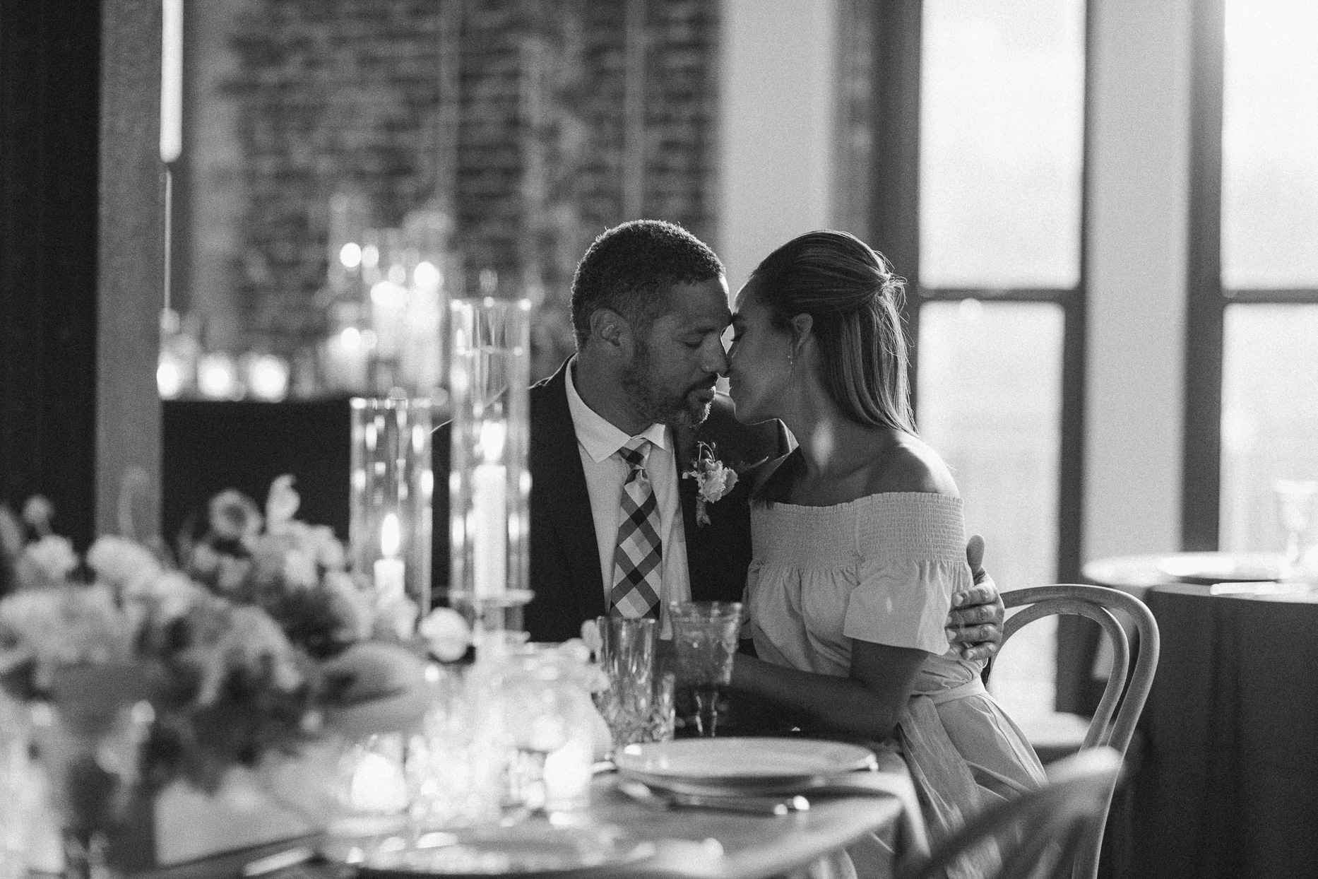 couple embracing at table during reception