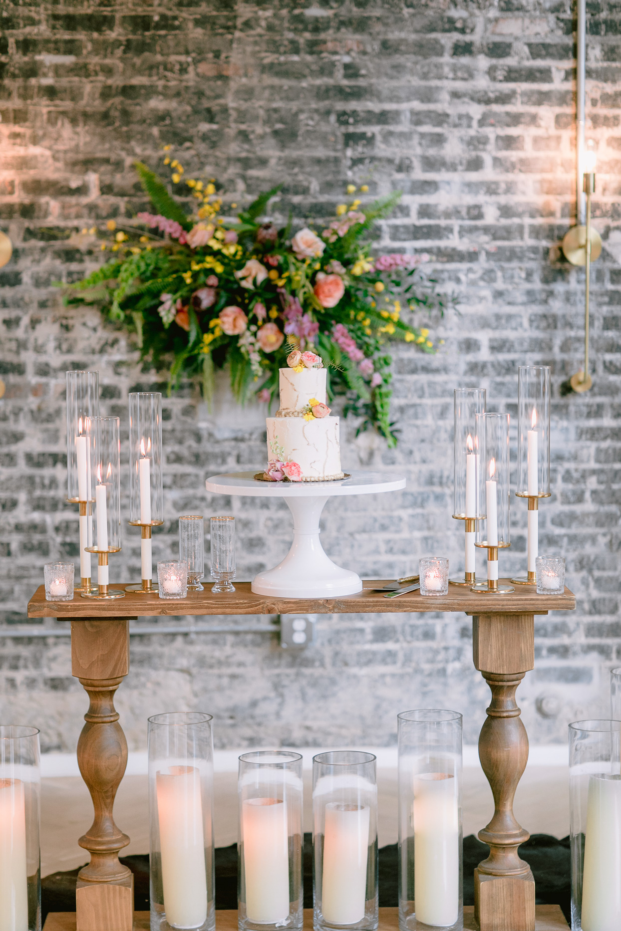 small cake on wooden table with candles and floral decor