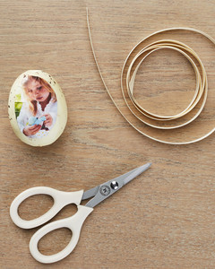 scissors ribbon and an egg with a photograph