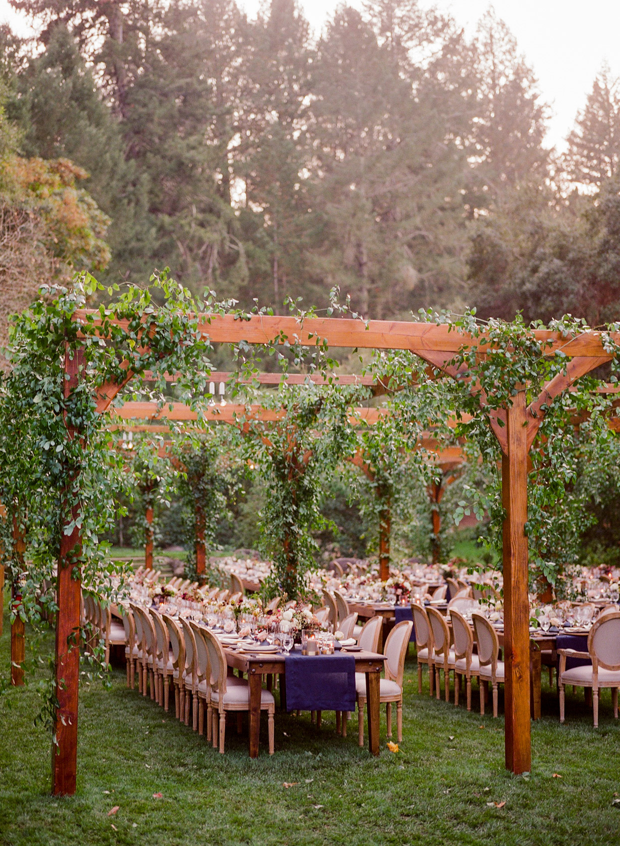 elegant outdoor wedding reception underneath wooden structure with vining greenery