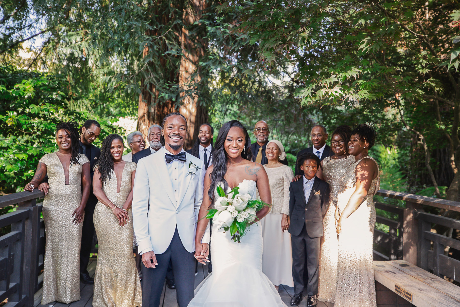 bride and groom with family in gold with lush greenery background