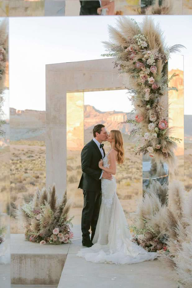 bride and groom kissing in desert with modern reflection architecture