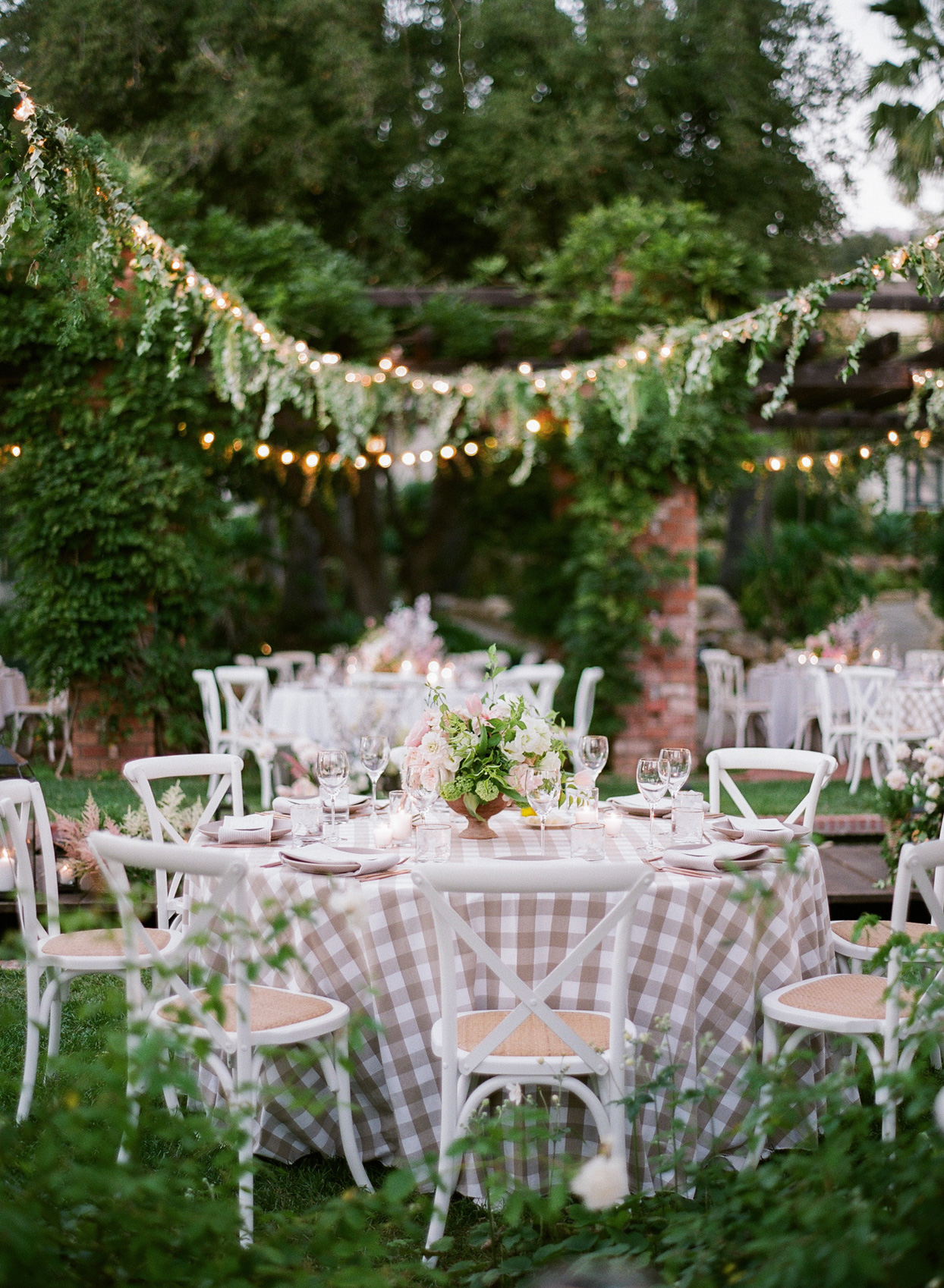 round tables with gingham clothes in garden reception