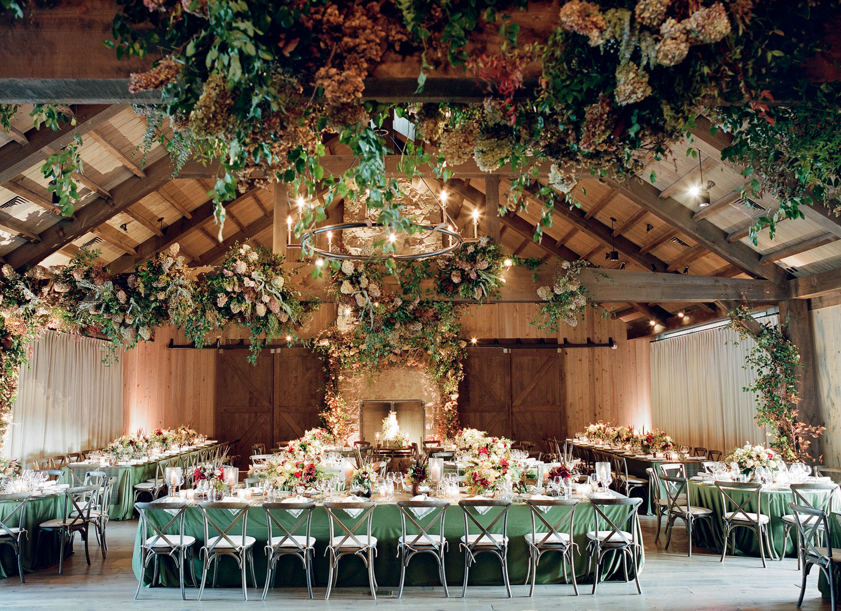 upscaled barn reception with long green tables and floral installments
