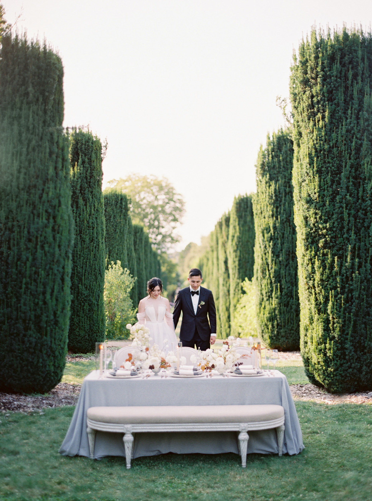 bride and groom walking to small reception table between row of tall trees
