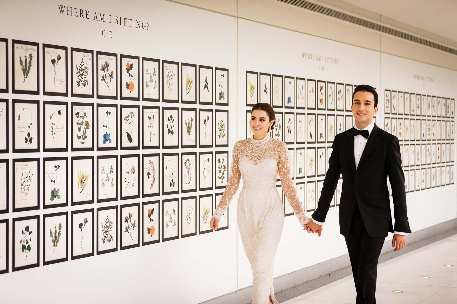 couple holding hands walking by pressed flower seating chart