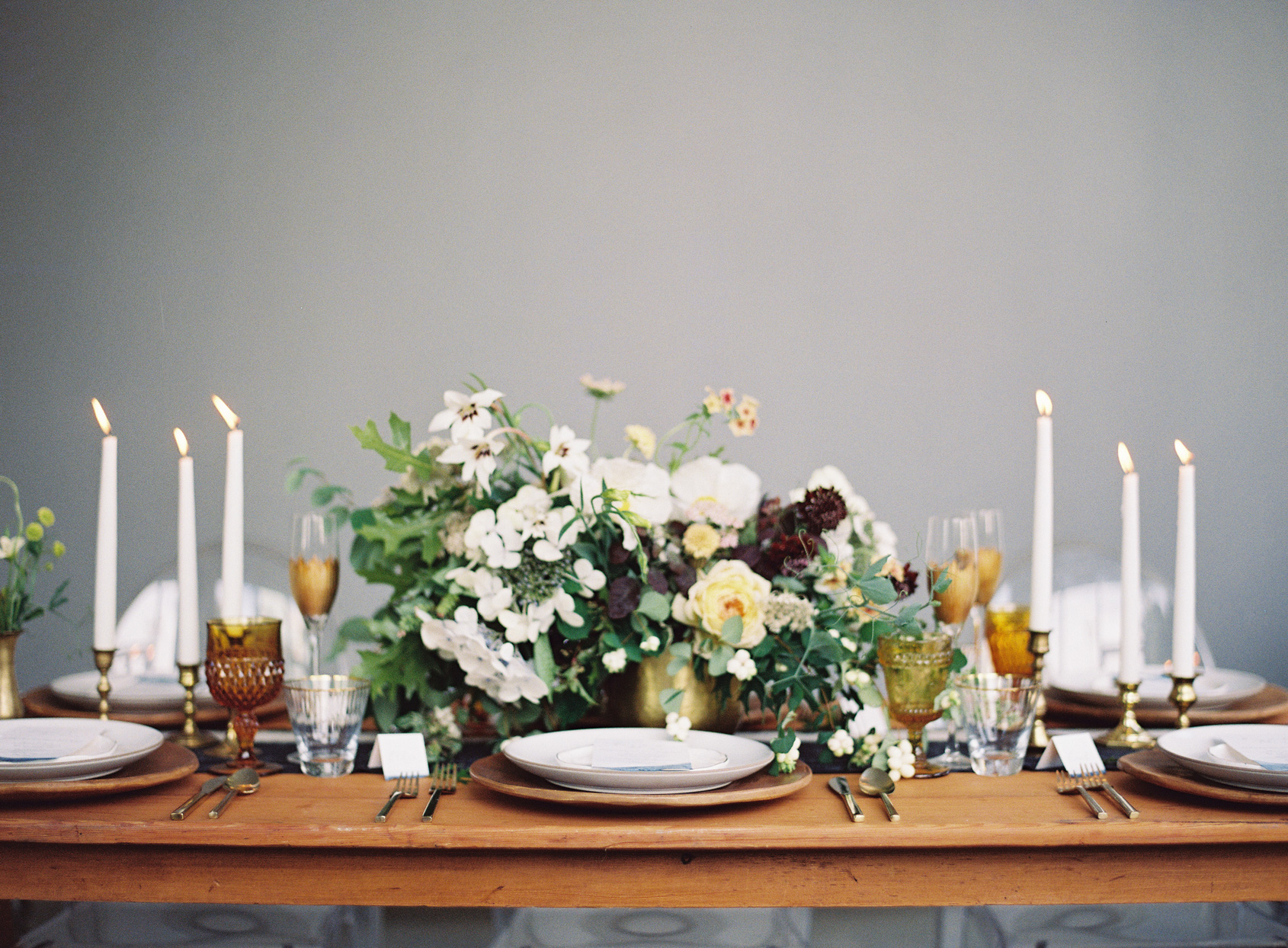 long wooden table with elegant floral bouquet and candles