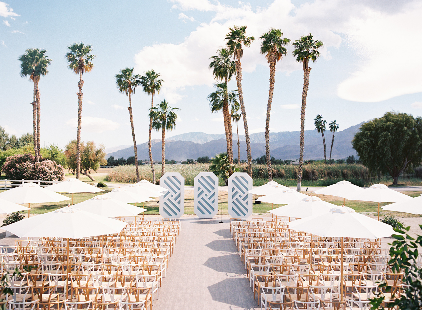 outdoor wedding ceremony with palm tree and mountain backdrop