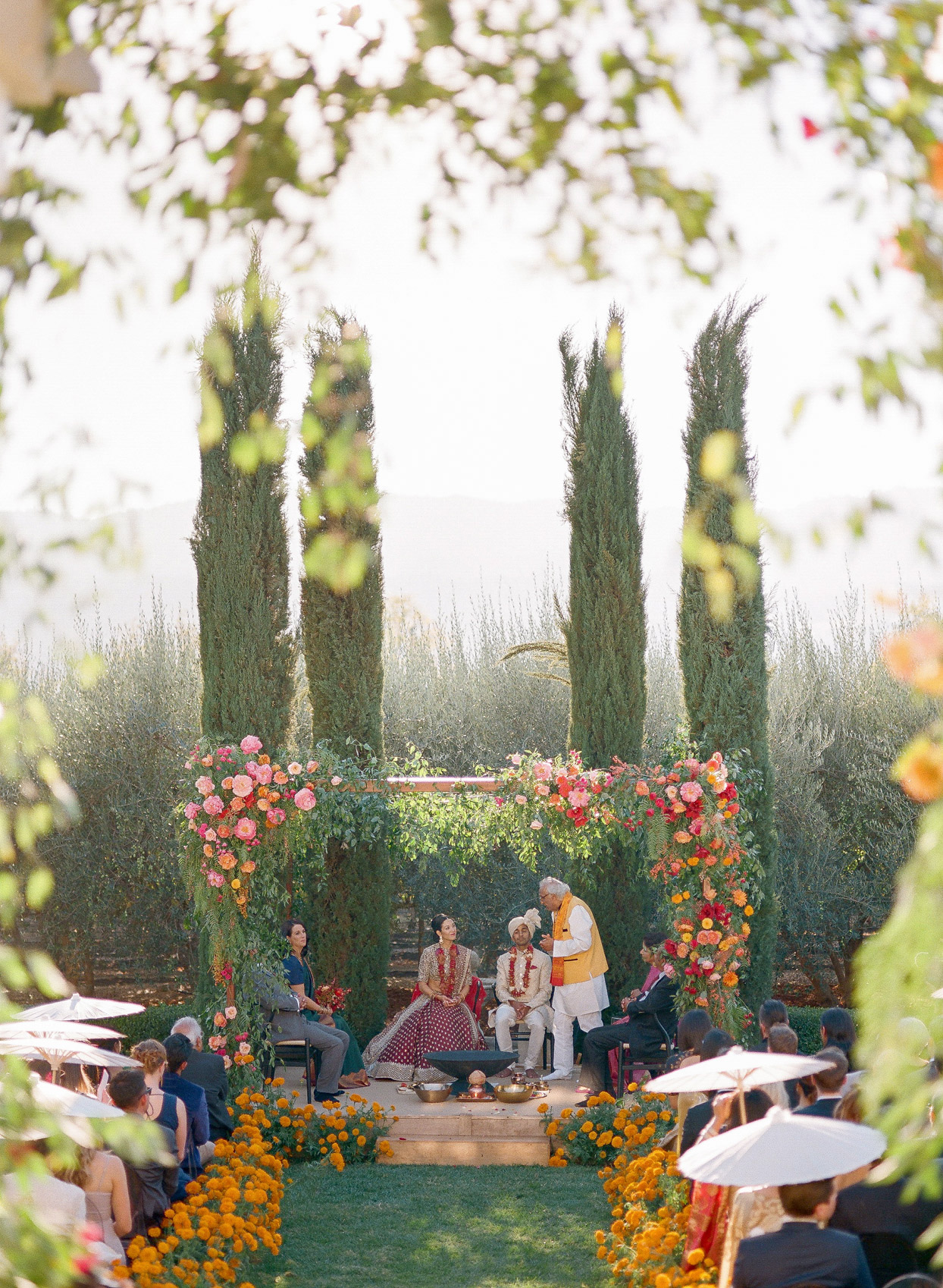 couple for Indian wedding ceremony under orange and pink floral arch