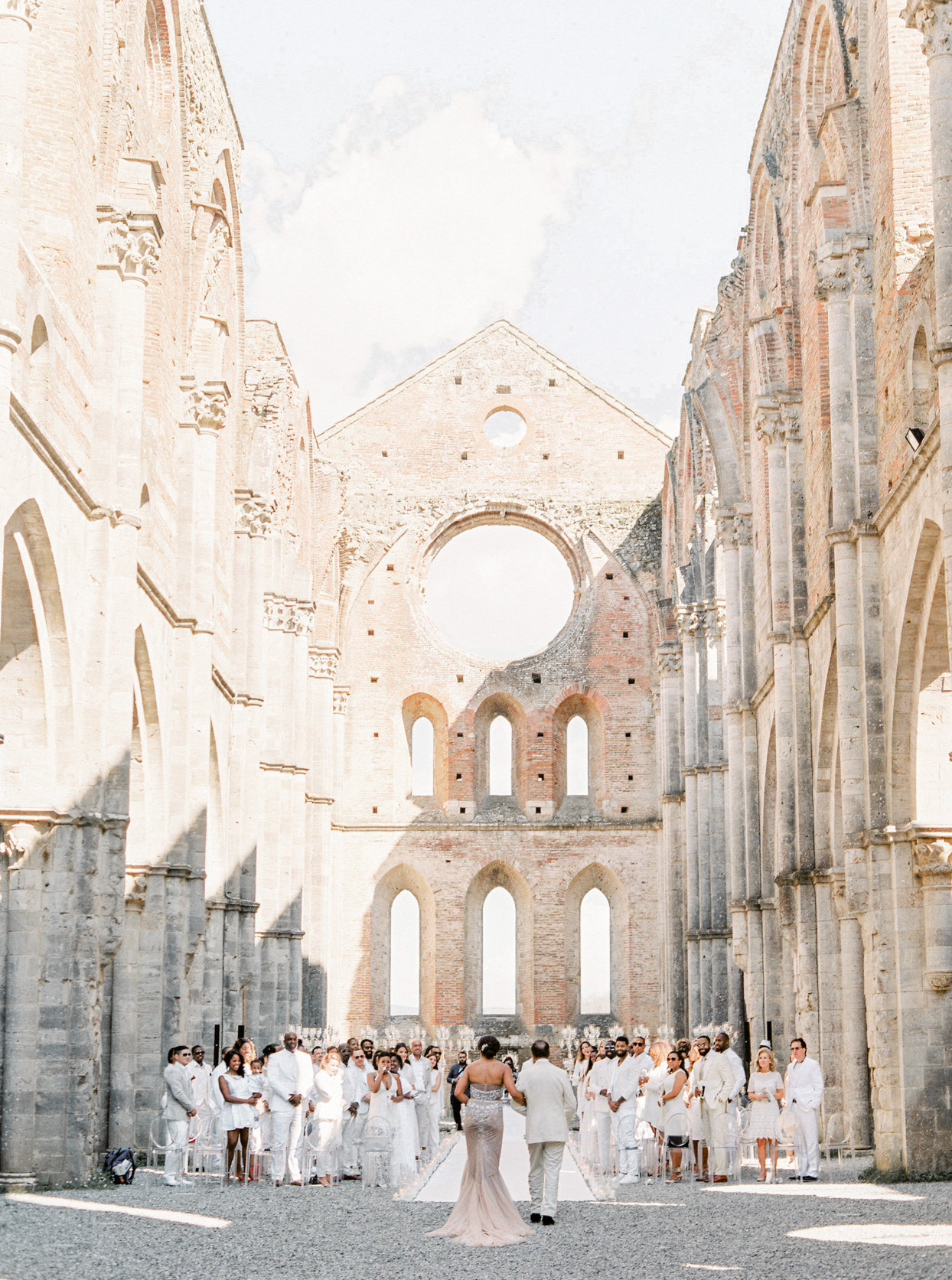 bride and father entering all white wedding ceremony in antique building