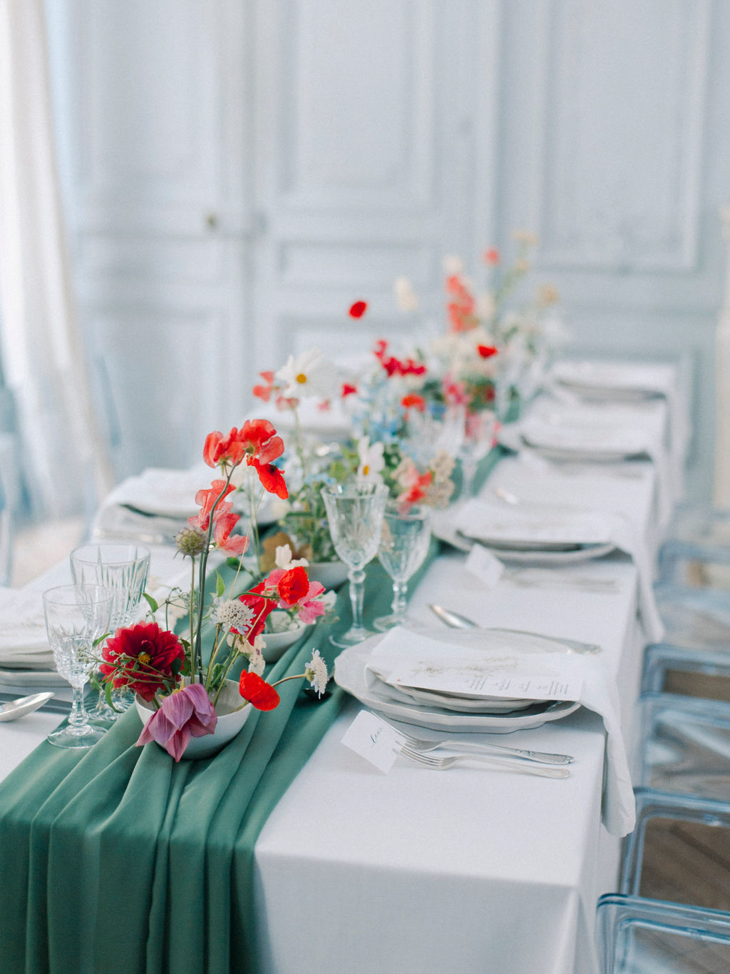 elegant wedding reception table with green runner and red flowers