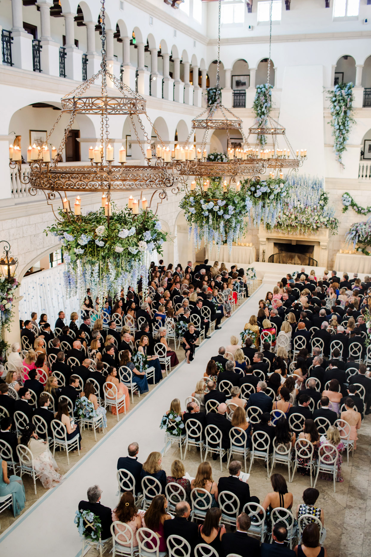 guests sitting in white chairs for indoor wedding ceremony with flowers hanging from chandeliers