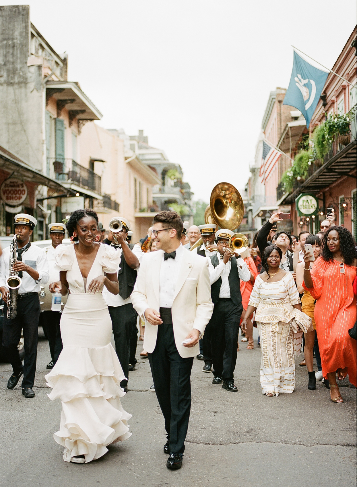 wedding party walking through streets with marching band