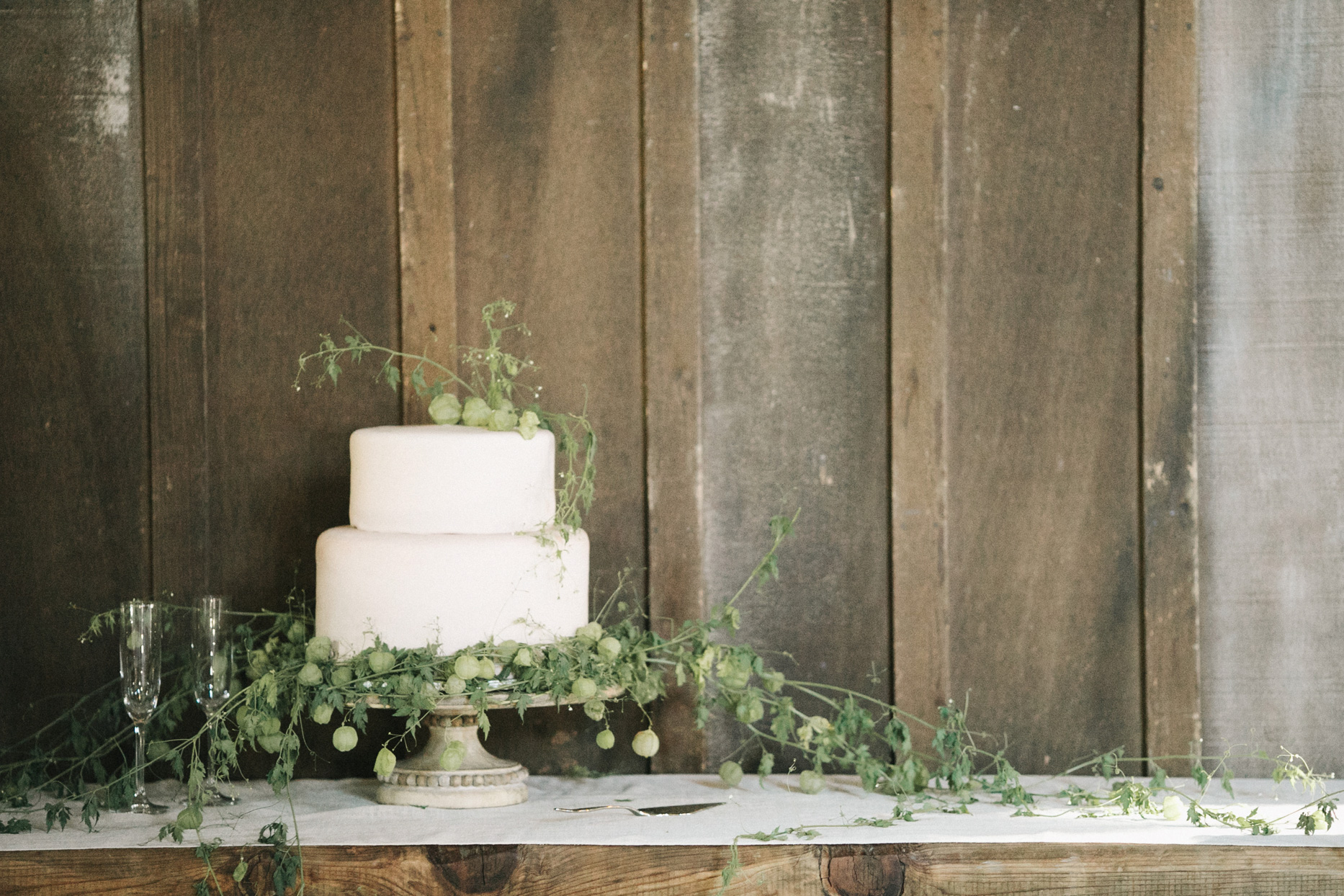 two-tier wedding cake at table against barn wall