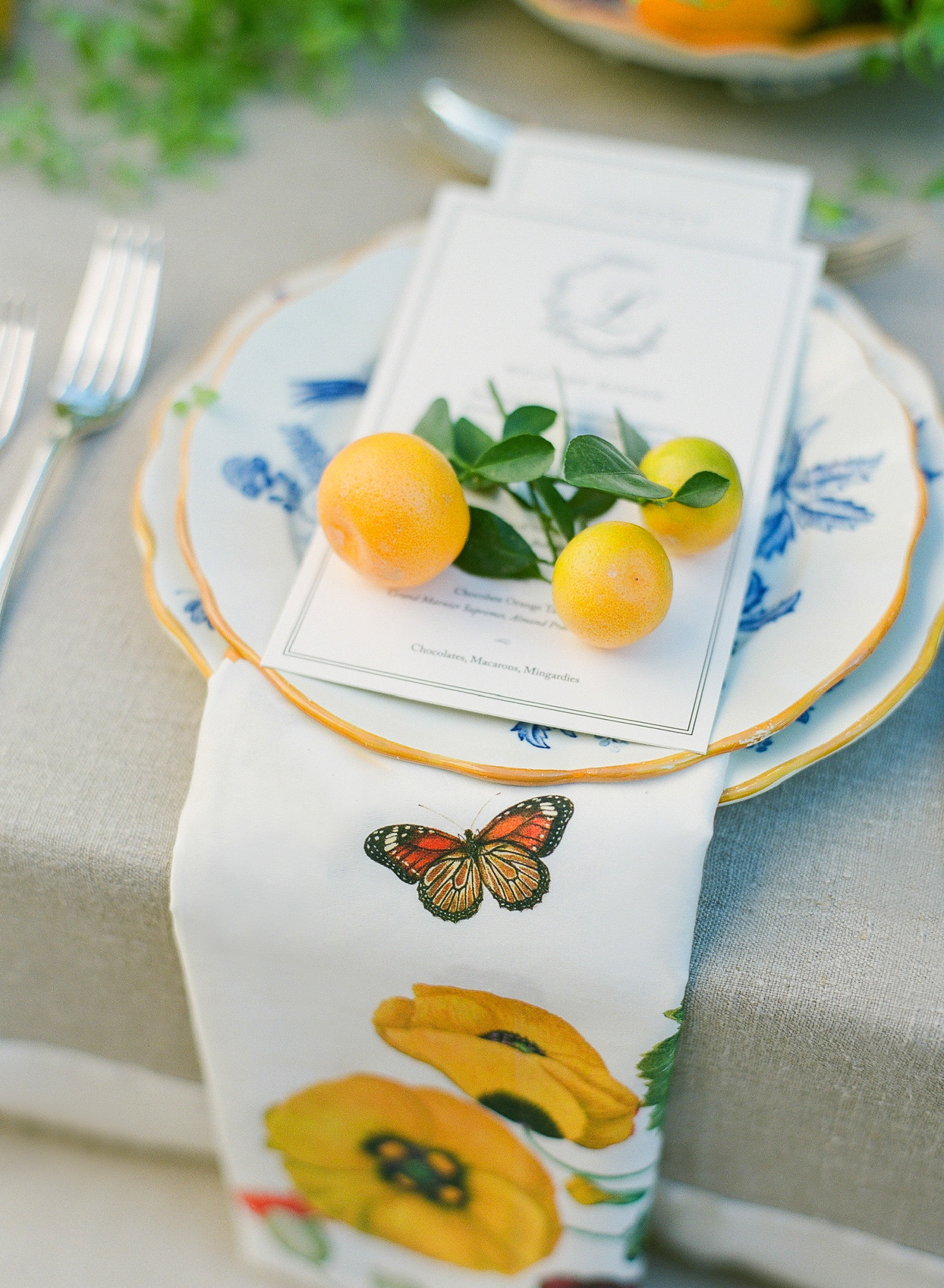 wedding place setting with orange citrus and floral decorations