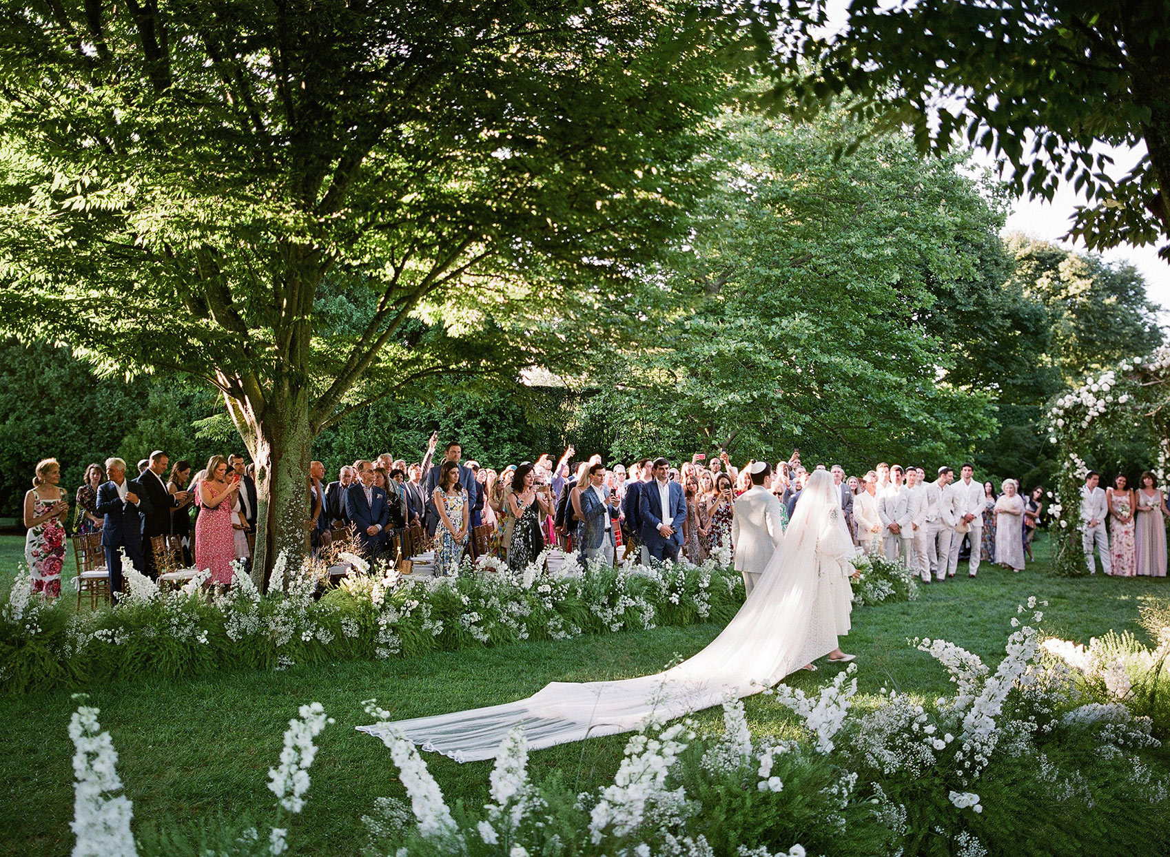 guests standing as bride processes at garden wedding