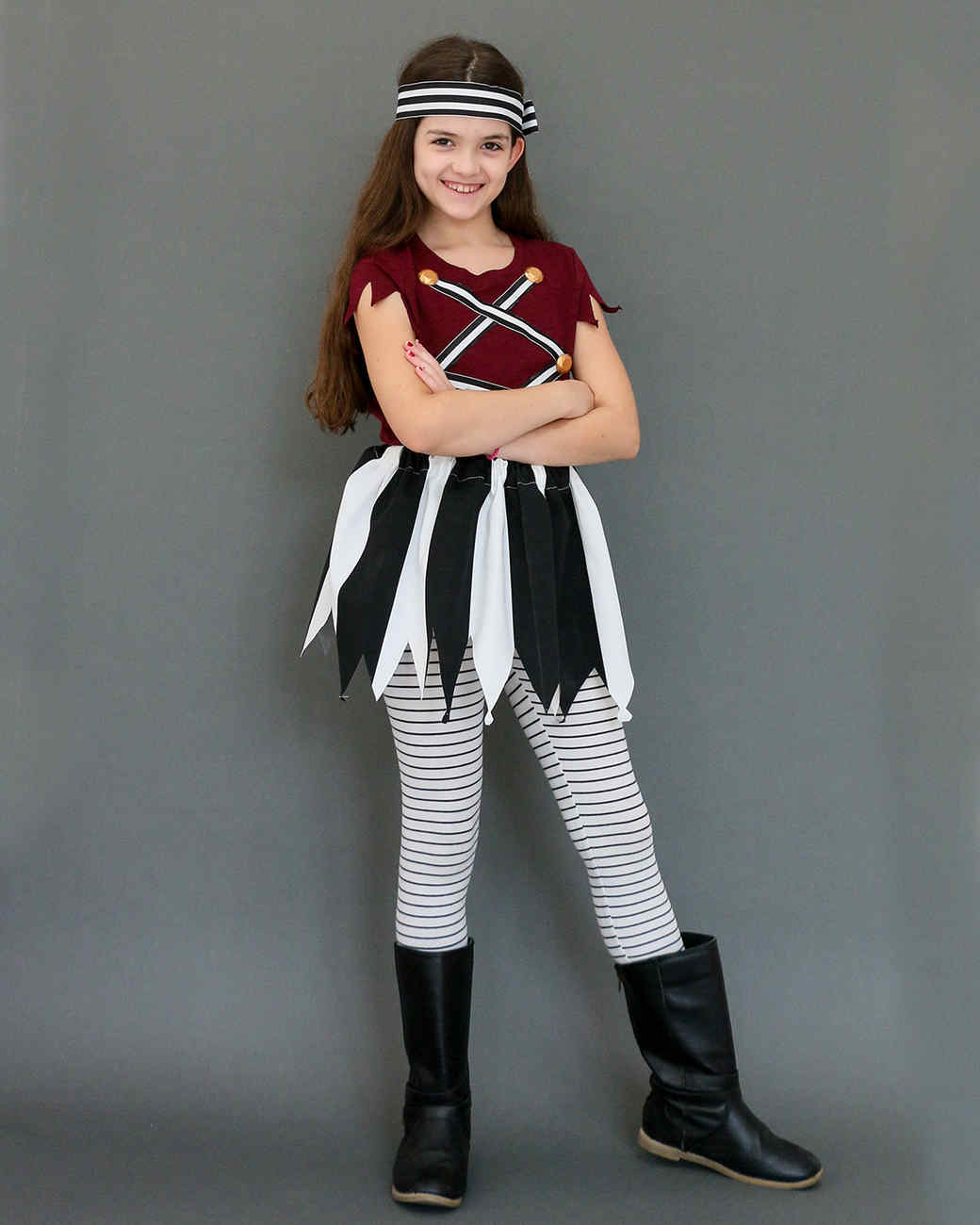 girl in pirate costume posing against gray background