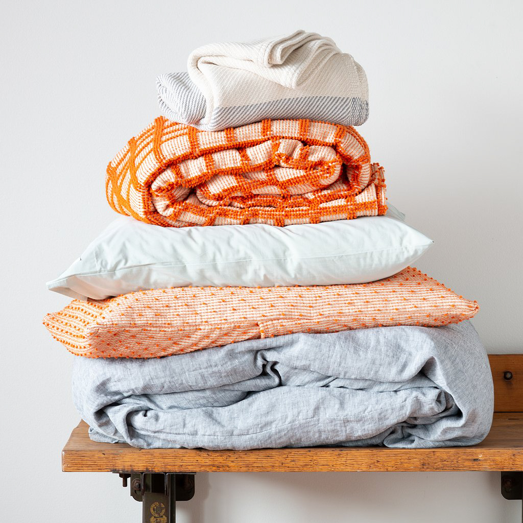 stack of orange and gray blankets on wooden bench
