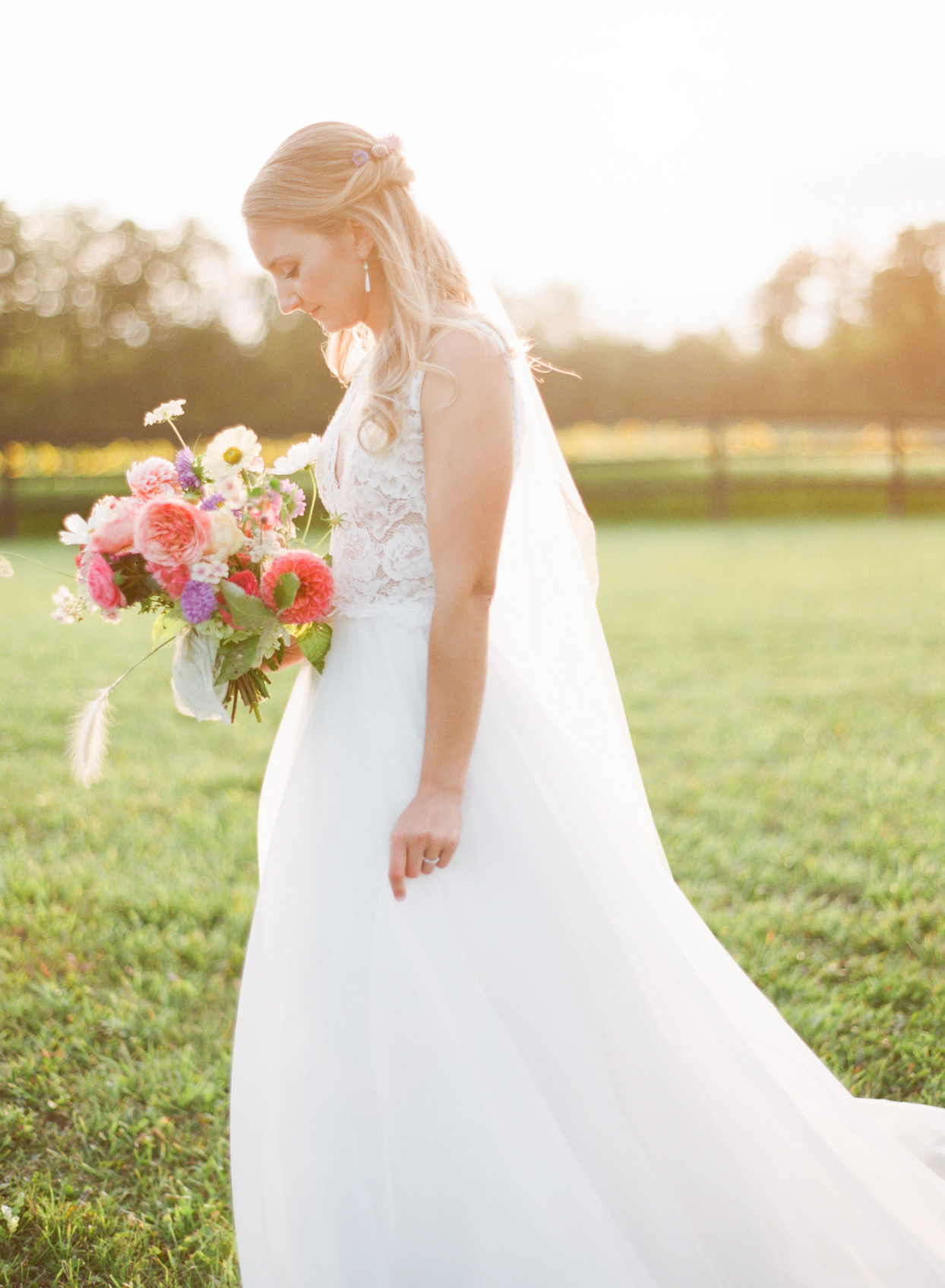 bride in sunny field holding colorful wedding bouquet