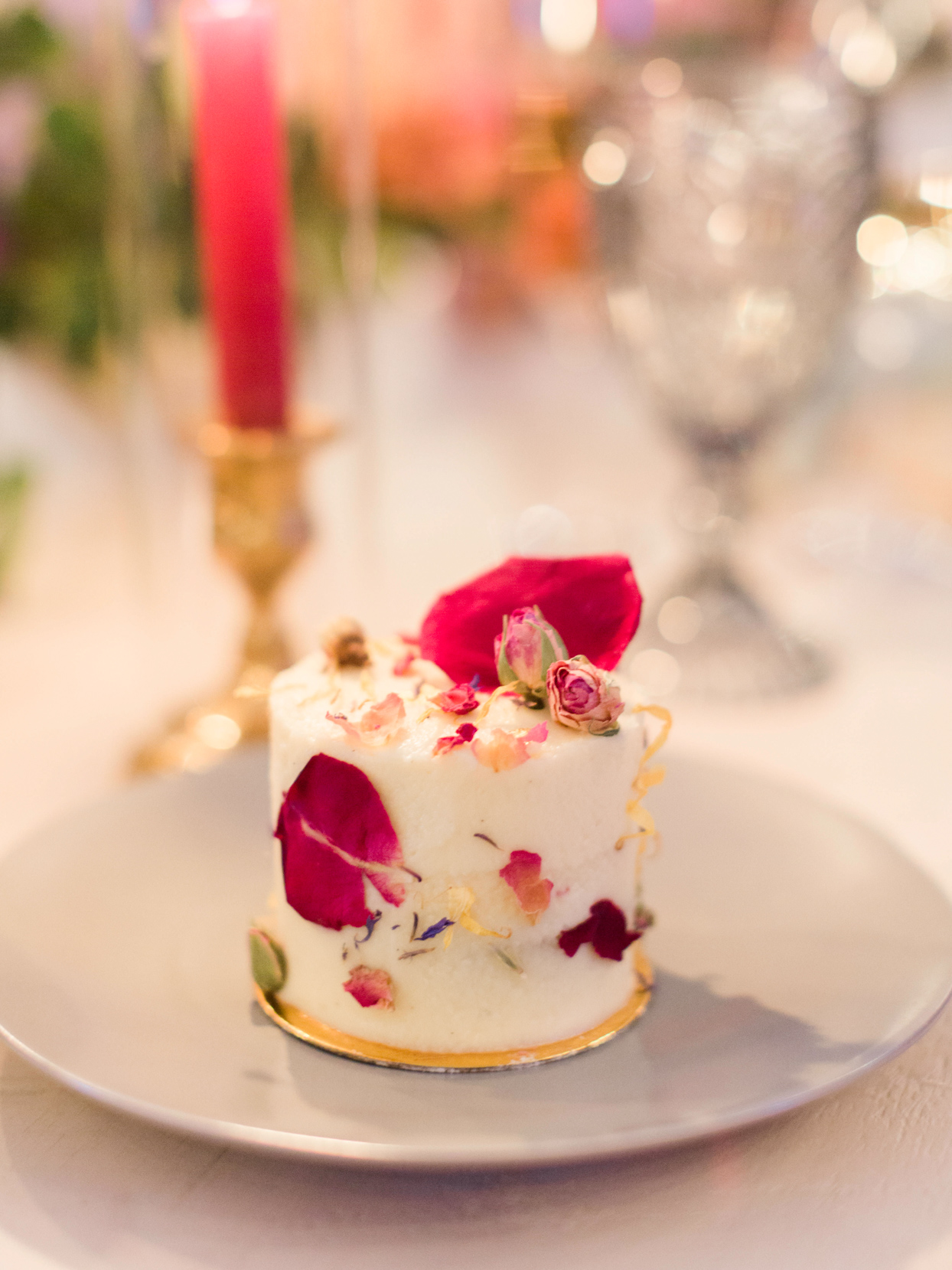 single layer wedding cake with pink flower petals