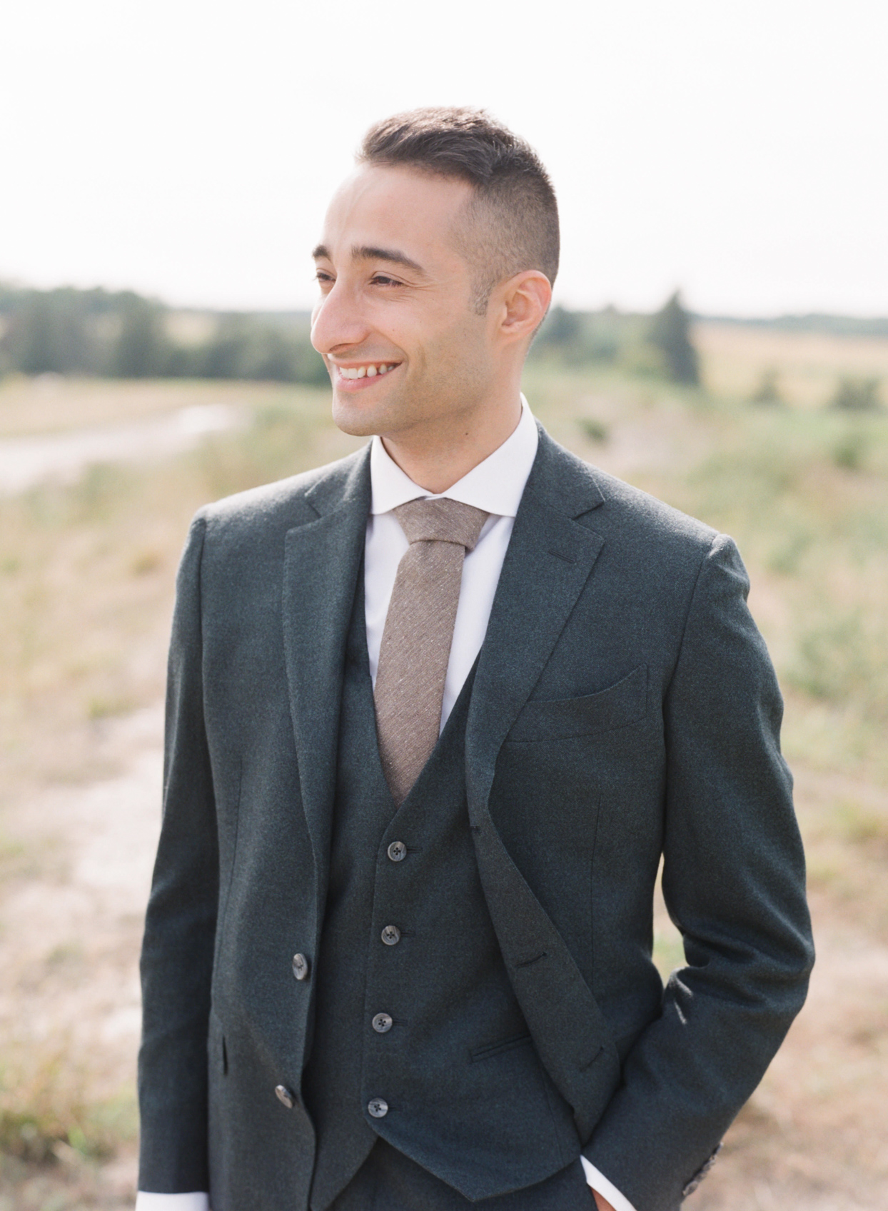 groom in soft gray suit and brown tie