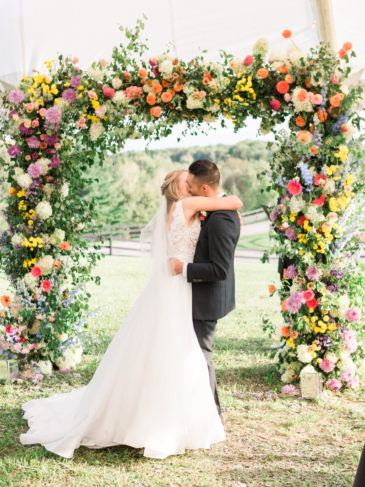 wedding kiss under colorful floral arch