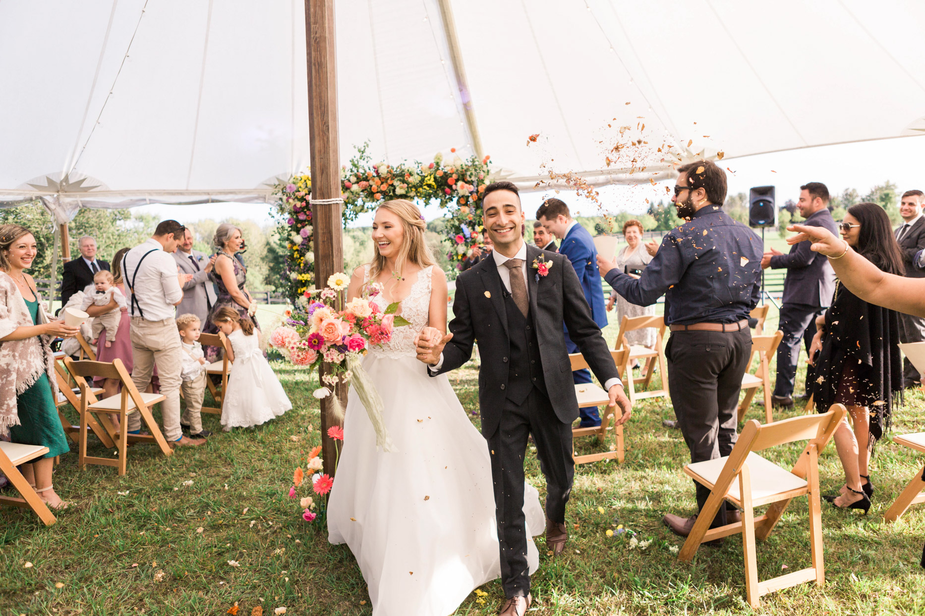 bride and groom smiling during recessional showered in flower petals