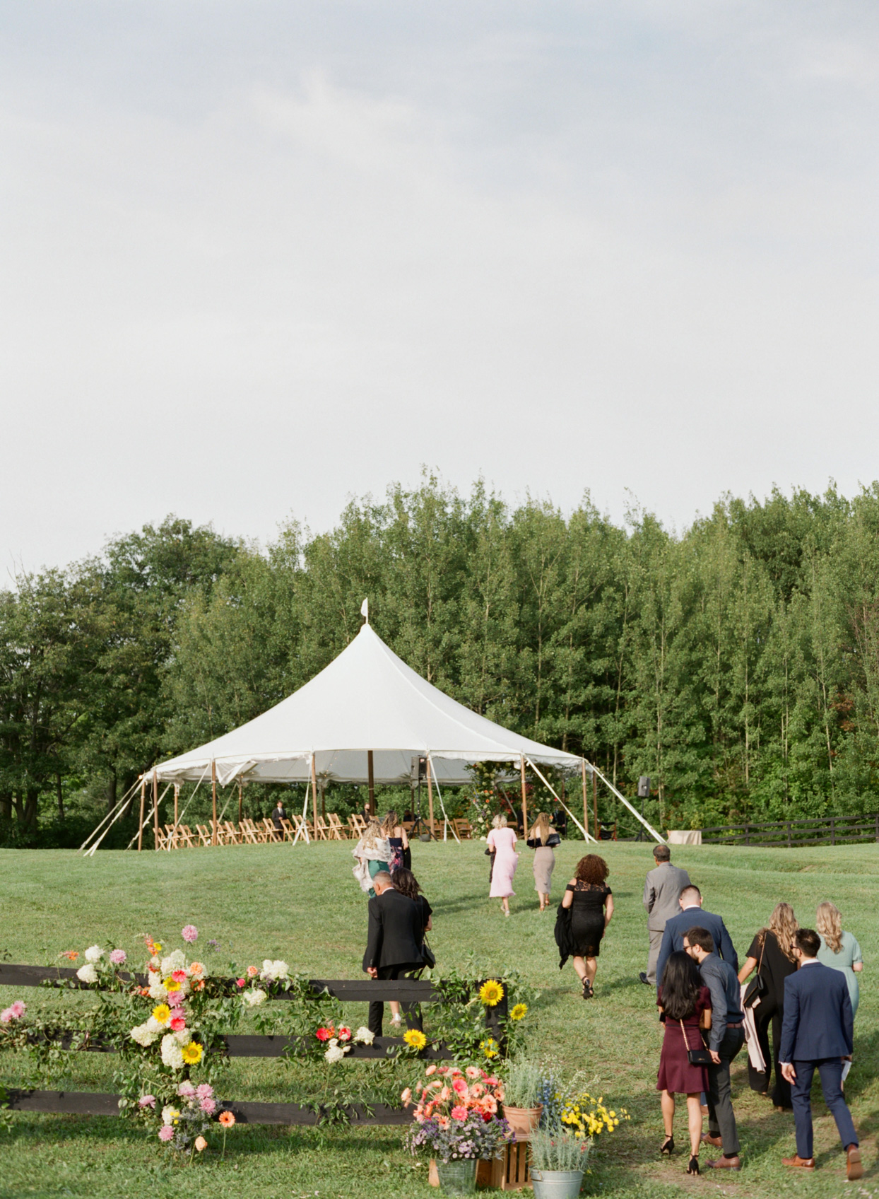 guests talking toward tent for wedding ceremony